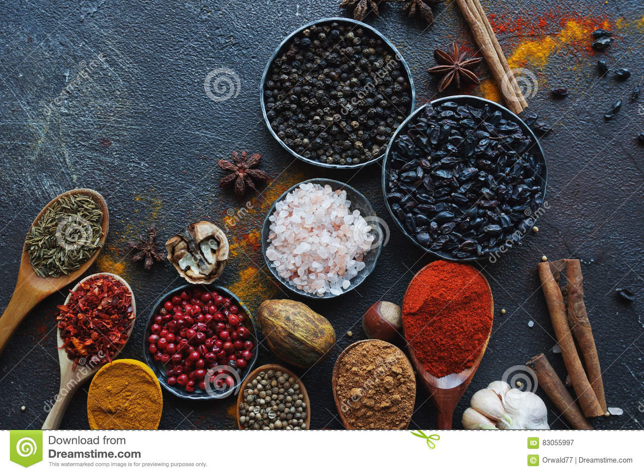 Various indian spices in wooden spoons and metal bowls and nuts on dark stone table. Colorful spices, top view