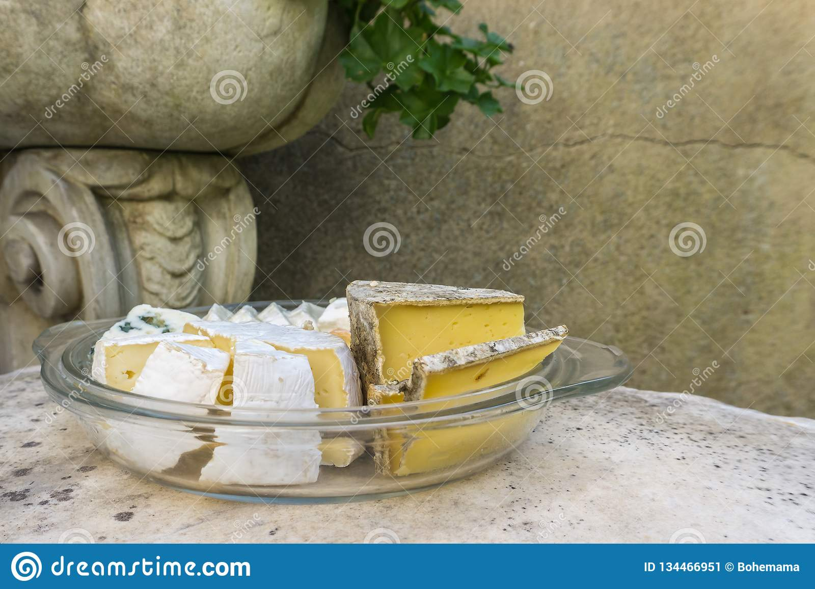 Various kind of cheese served on stone table in vintage exterior