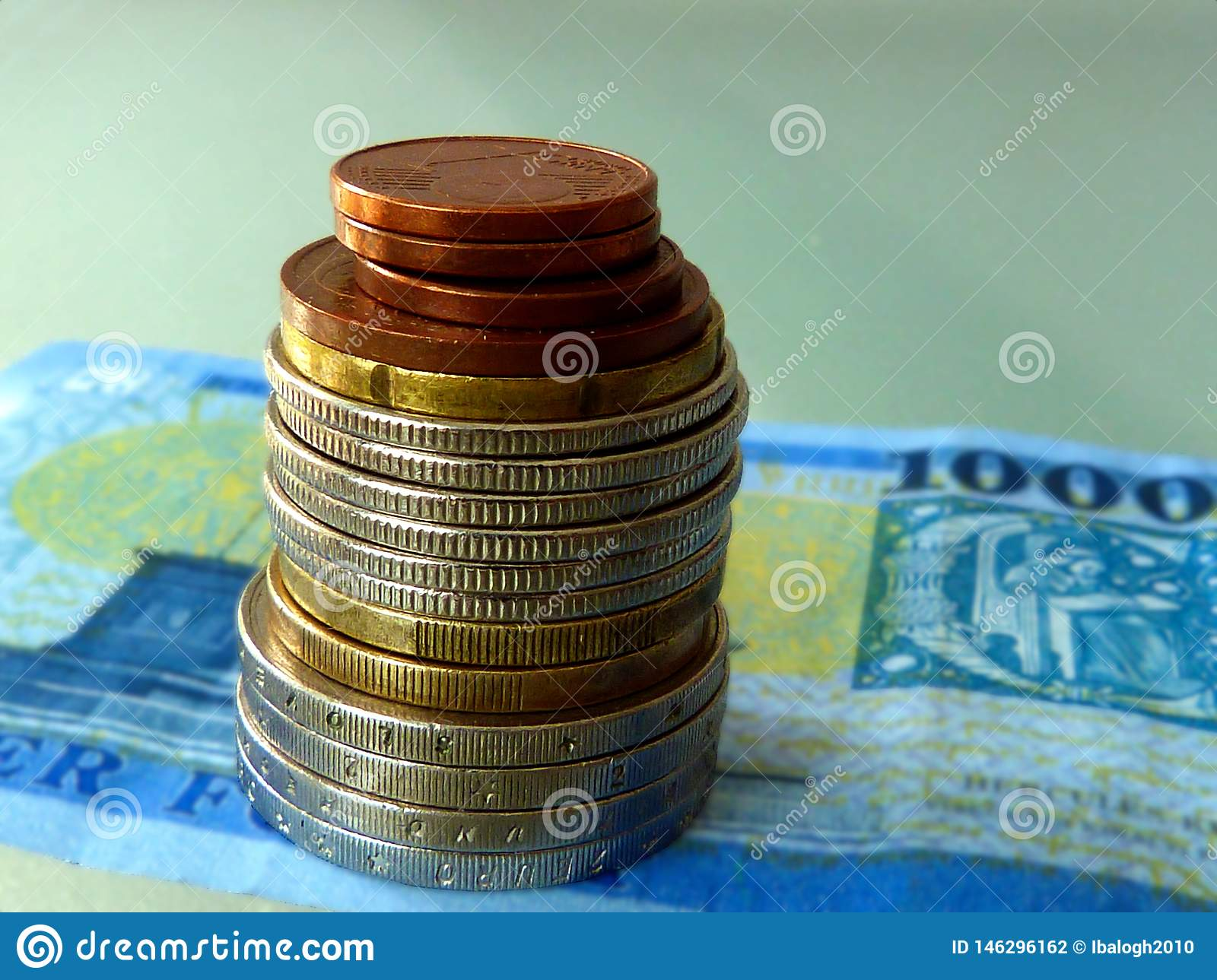 Various nickel and copper color  coins stacked on paper bill