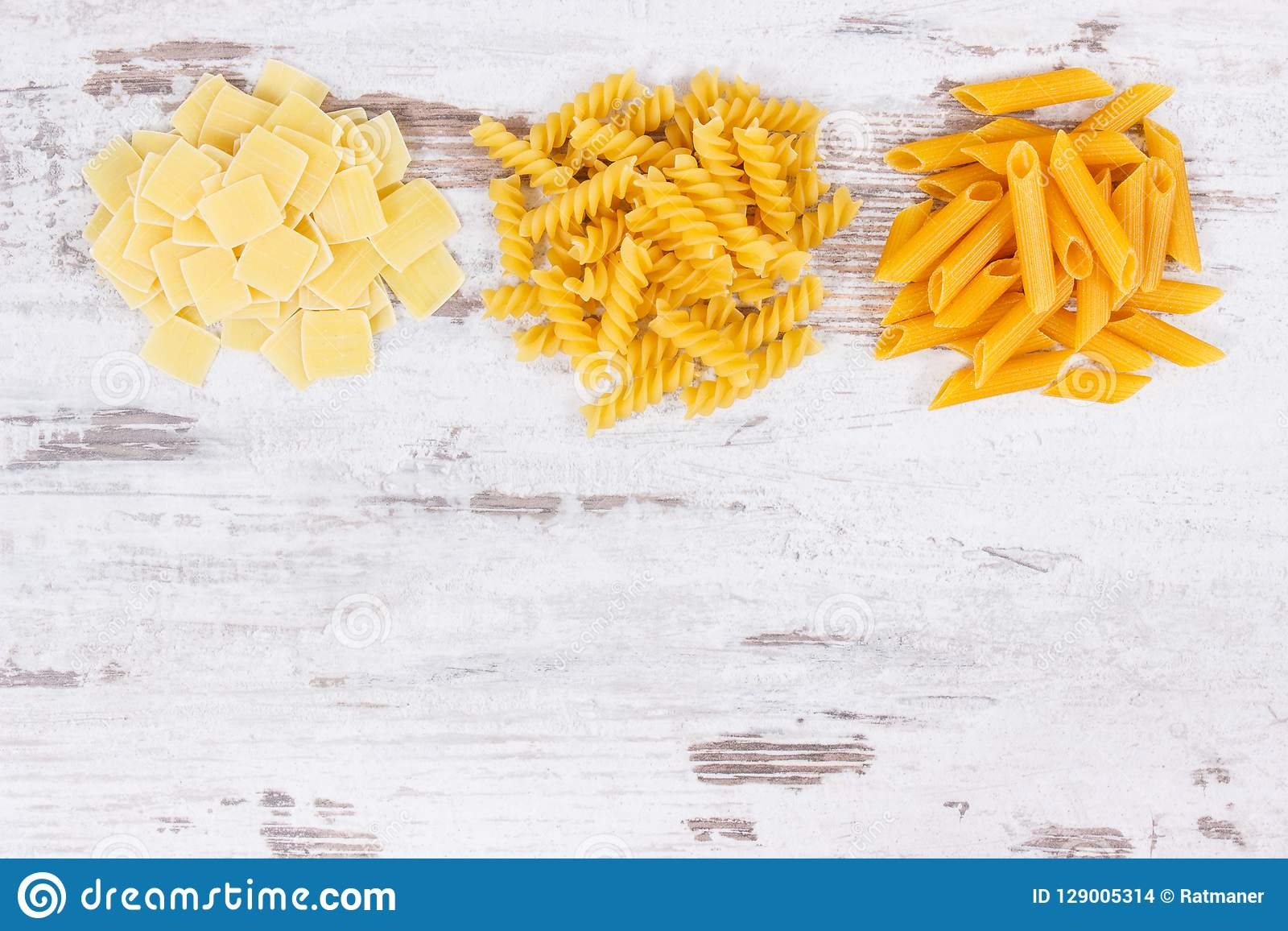 Various pasta as ingredients containing carbohydrates and dietary fiber, healthy nutrition, copy space for text