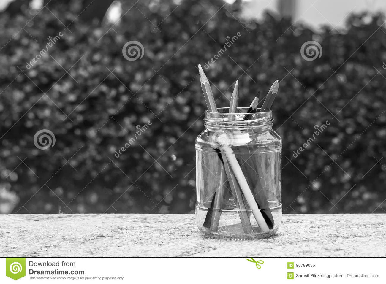 Various pencil in glass bottle on concrete floor with green bush background