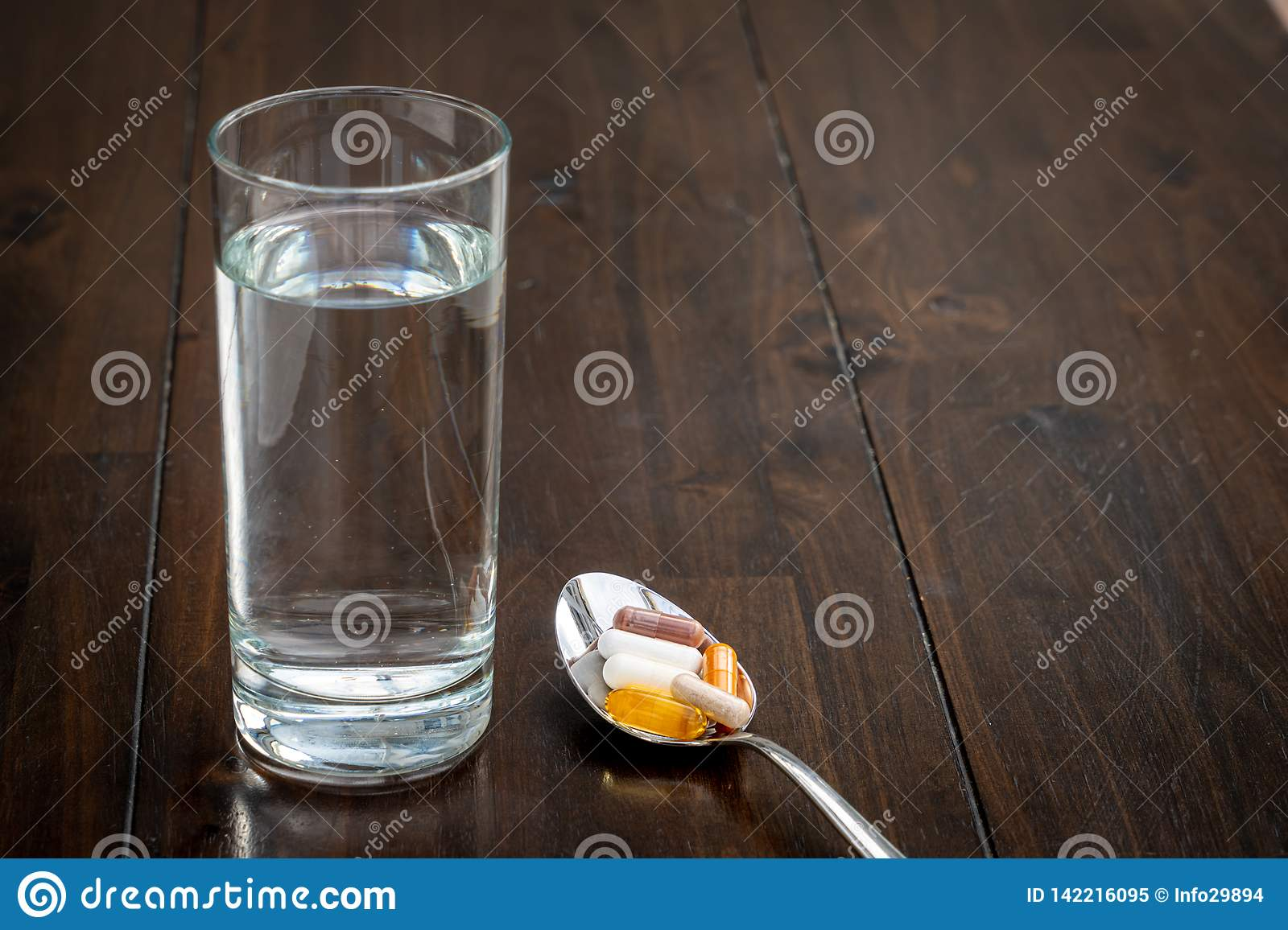 Various pills are on a spoon next to a glass of water on a brown table