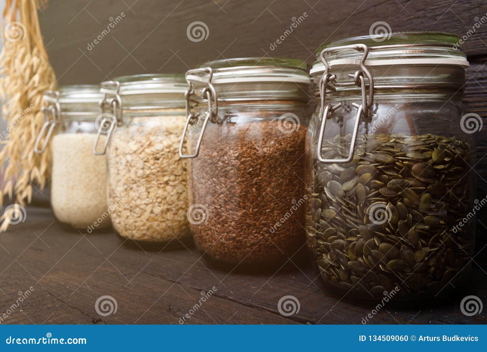 Various seeds in storage jars in pantry, dark wooden background. Smart kitchen organization