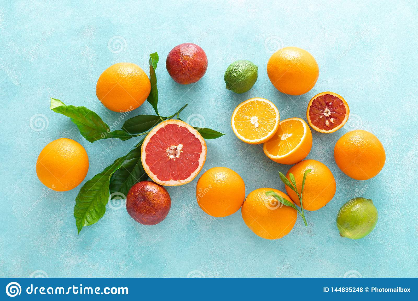 Various tropical fruits composition with leaves, flat lay blue summer background