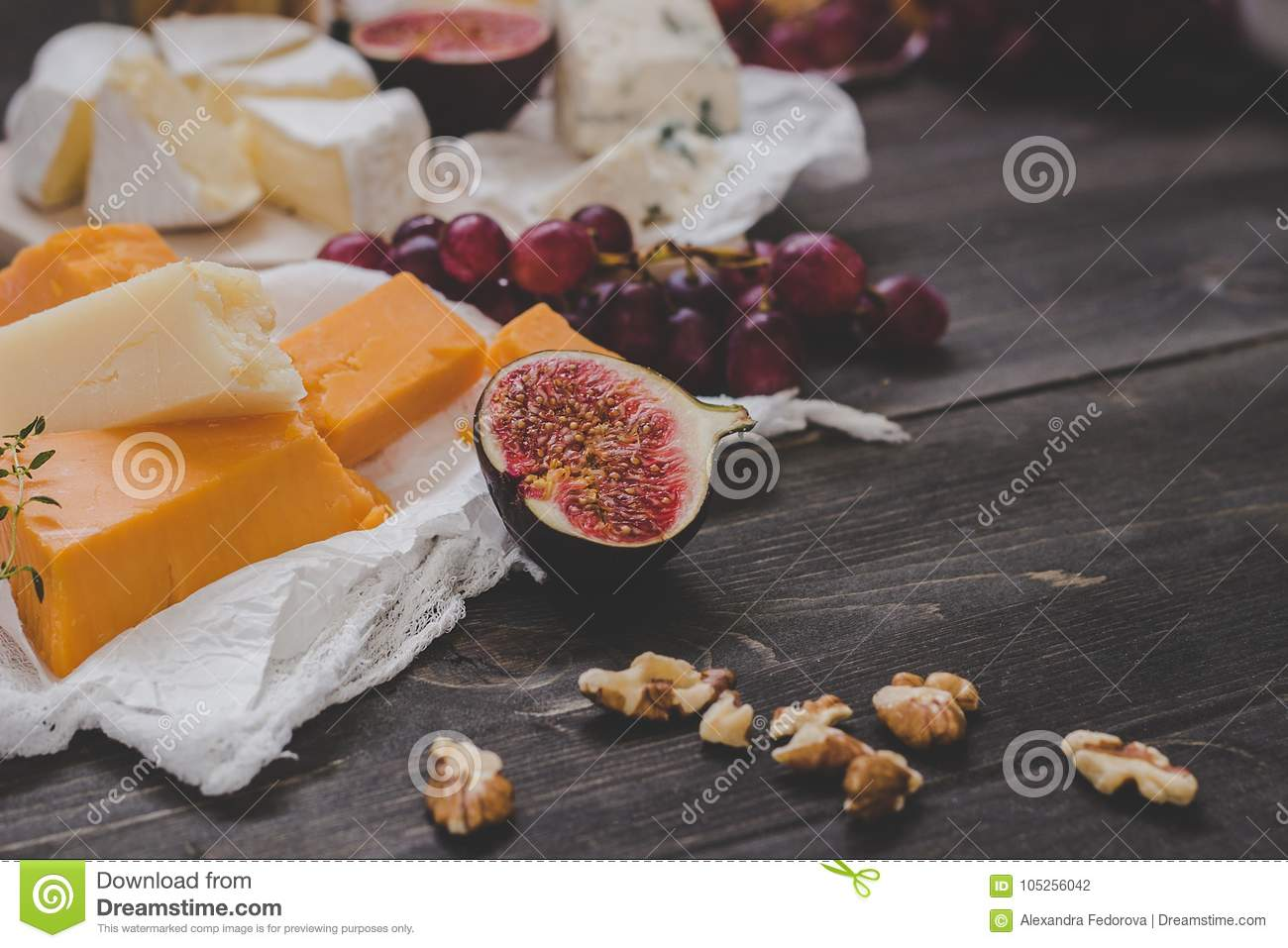 Various types of cheese with fruits and nuts on the wooden dark table. Selective focus