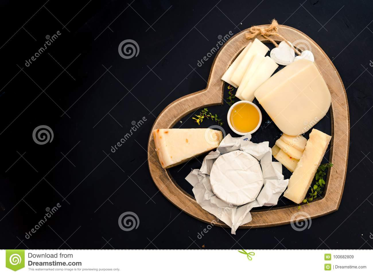 various types of cheese on a stand in the shape of a heart, concept elegant life and love cheese, top view
