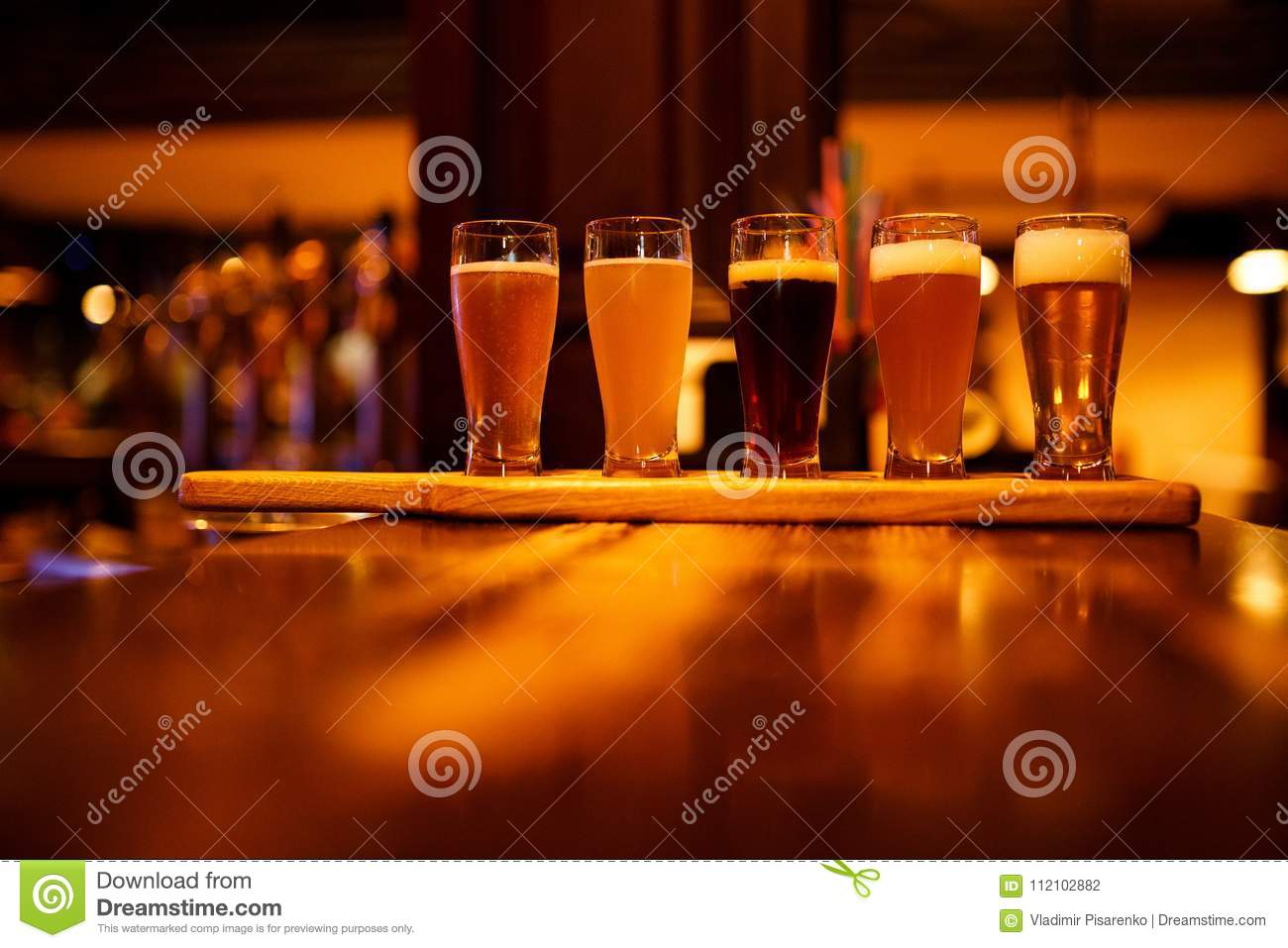 Various types of craft beer in small glasses on a wooden table in a pub.
