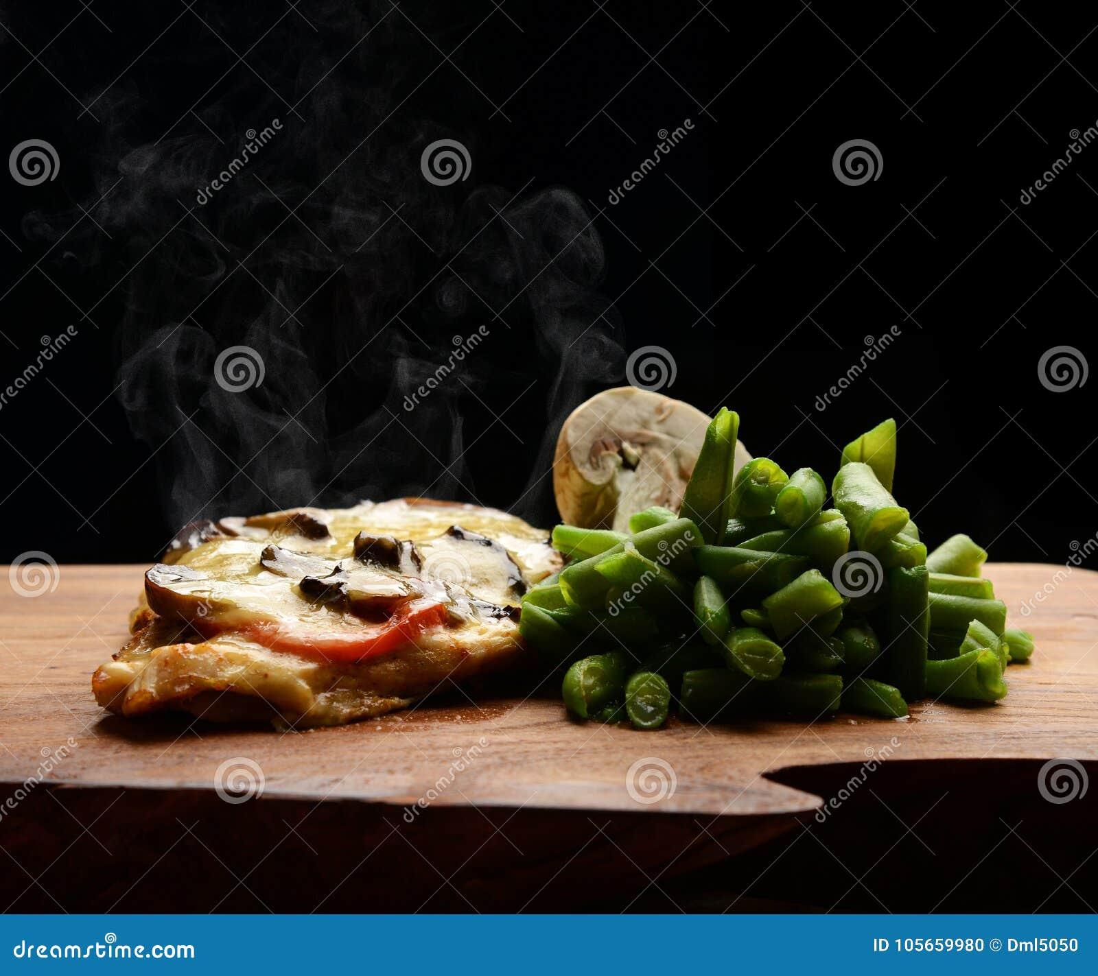 Varkenskotelettenlapje vlees met de gesmolten paddestoel s van kaastomaten en gestoomde bonen op rustieke houten plaat