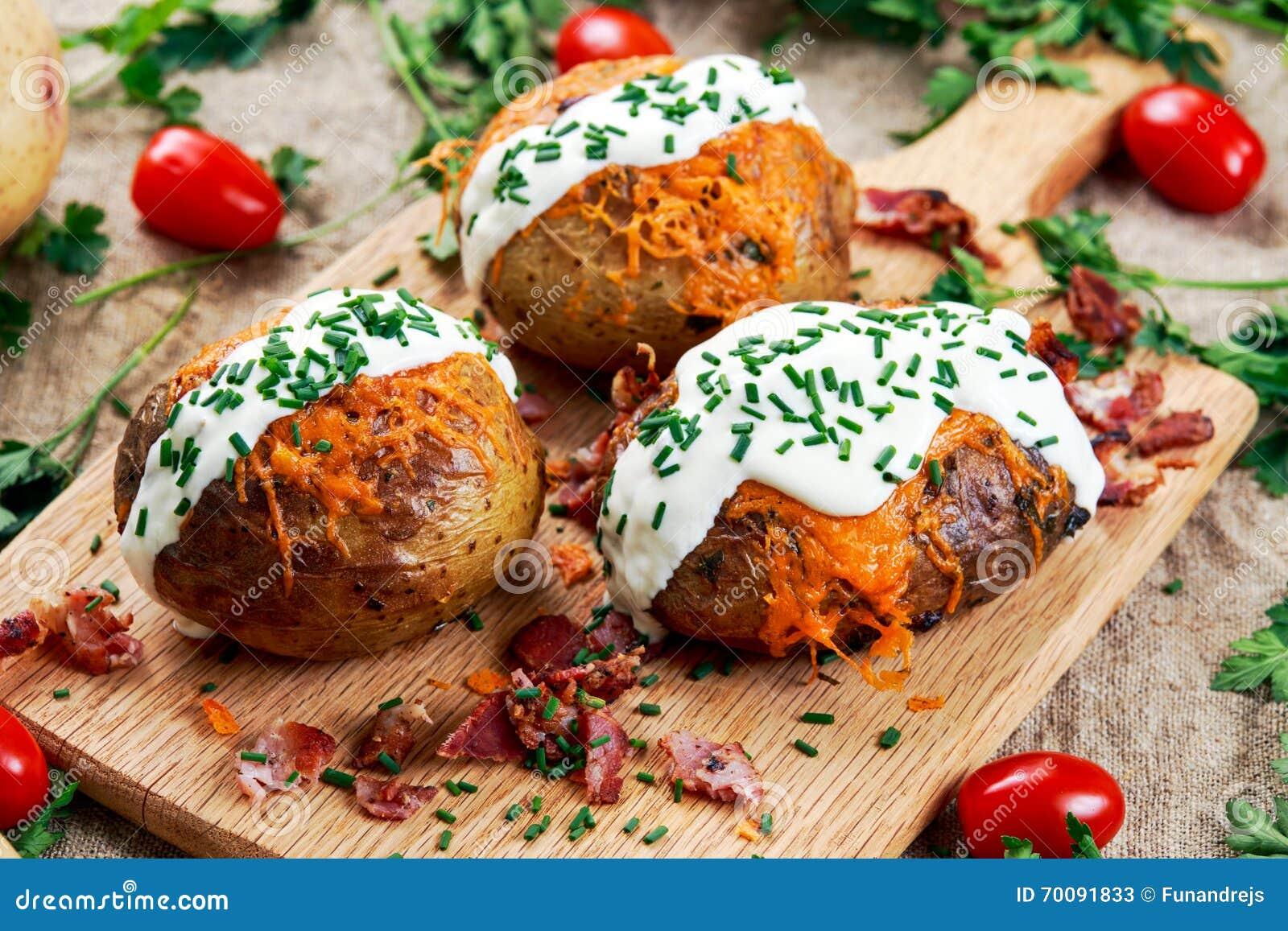 Varm bakad potatis med ost, bacon, gräslökar och gräddfil