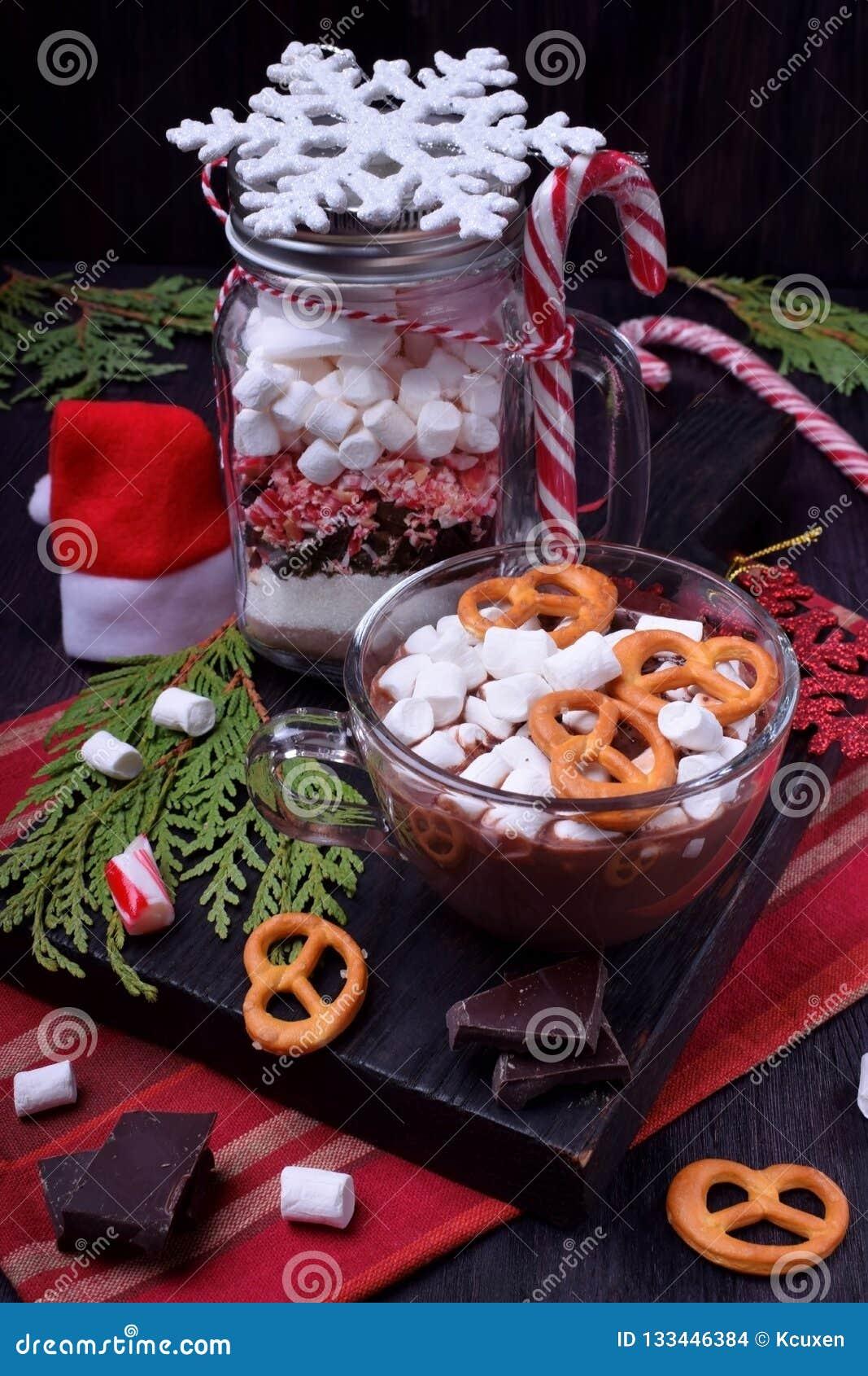 Varm choklad med marshmallower och kringlor i en kopp och en torr blandning för att förbereda drinken