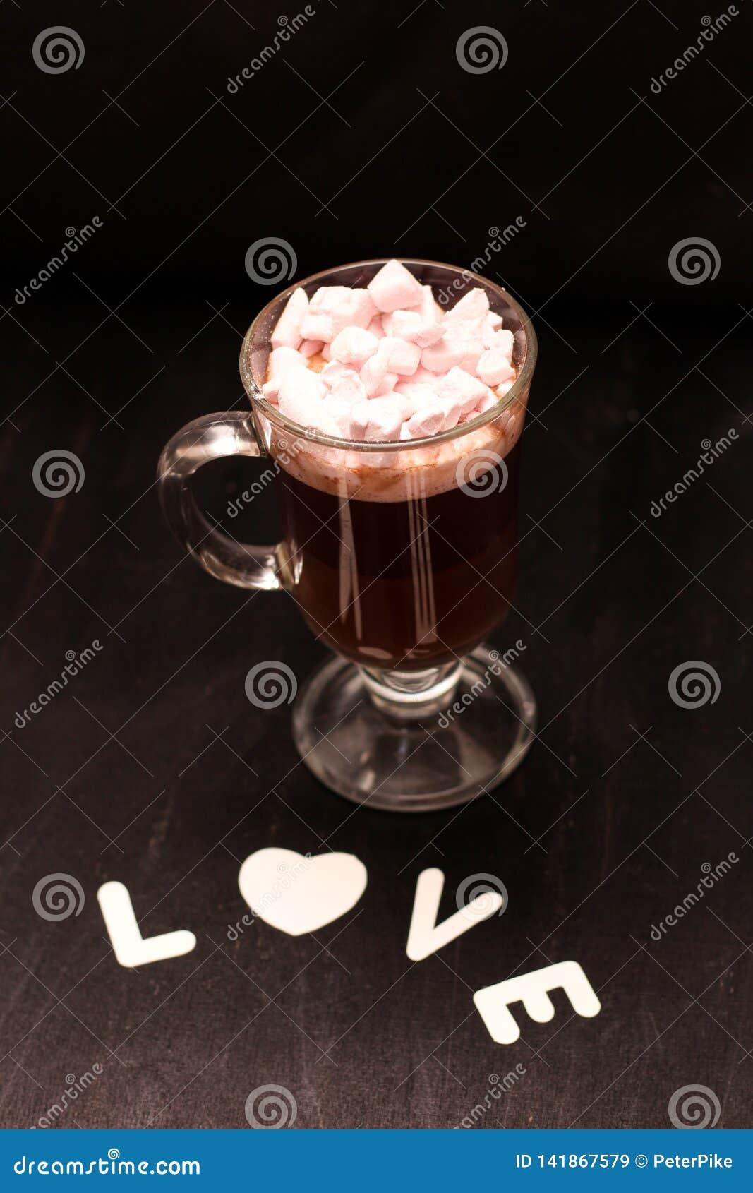 Varm drink i en exponeringsglaskopp med rosa marshmallower