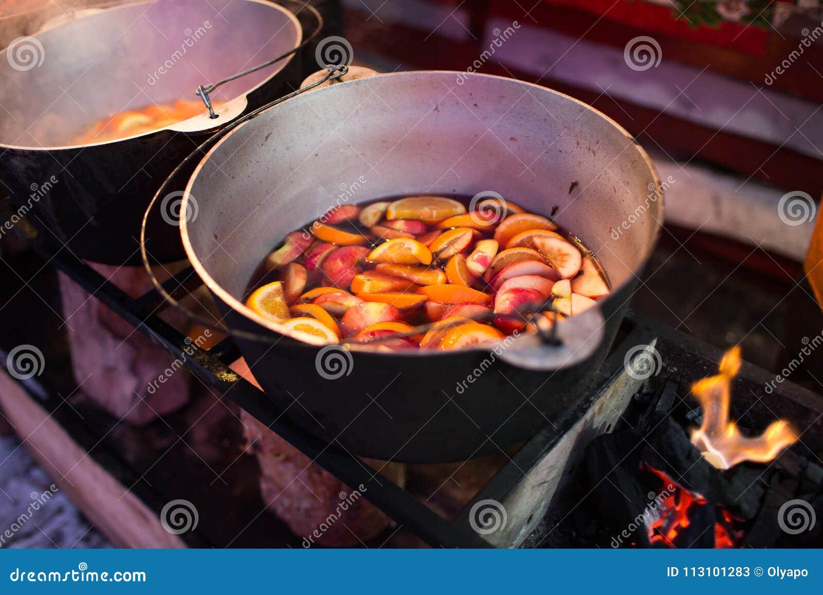 Varm gluhwein eller funderat vin i en kittel på mässan, lokal fest, varmt och kryddigt En varm hälsosam traditionell citrus drink