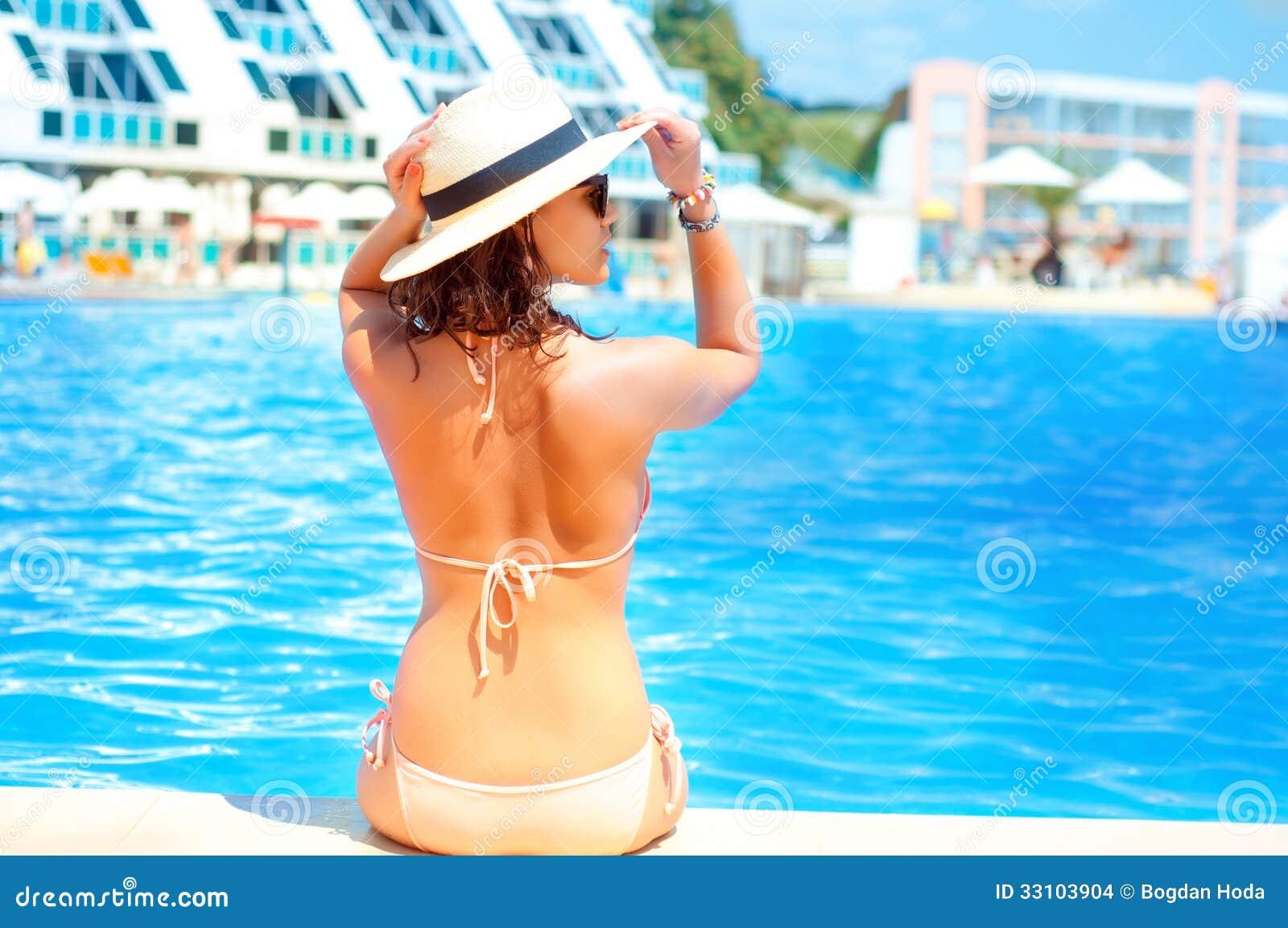 Varm härlig kvinna i hatt- och bikinianseende på pölen
