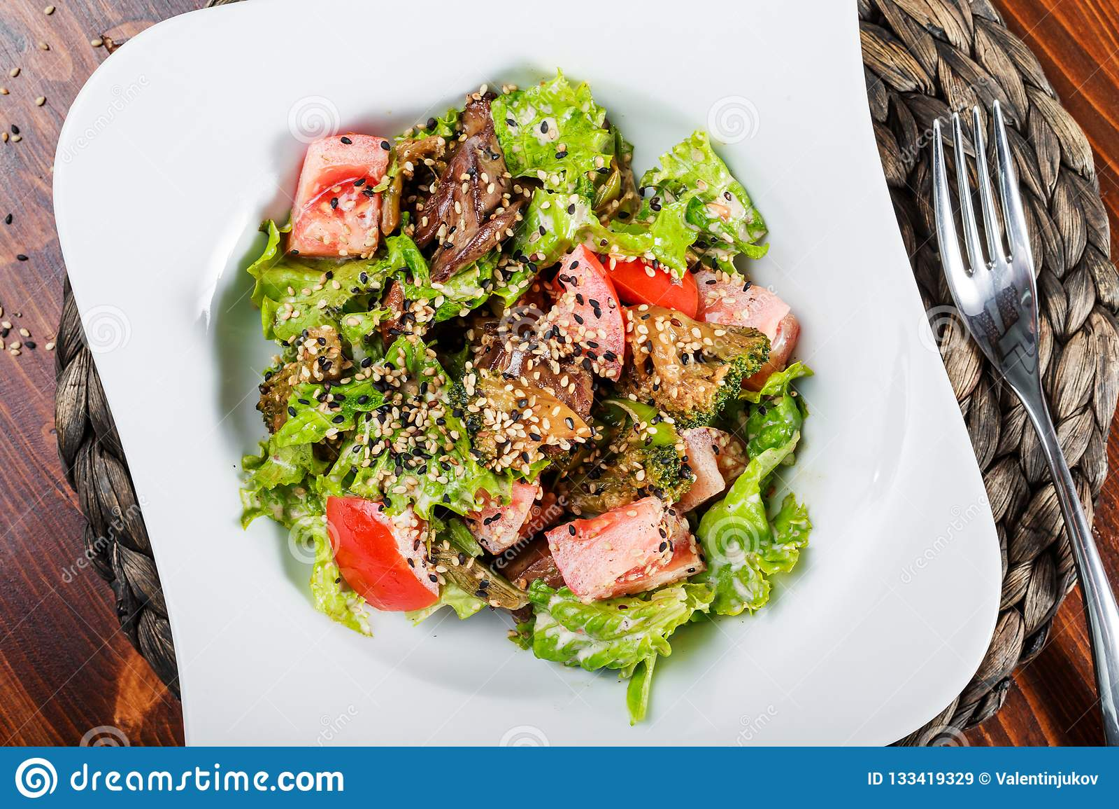 Varm sallad med feg lever, tomater, grönsallatsidor, broccoli på trätabellen sund mat