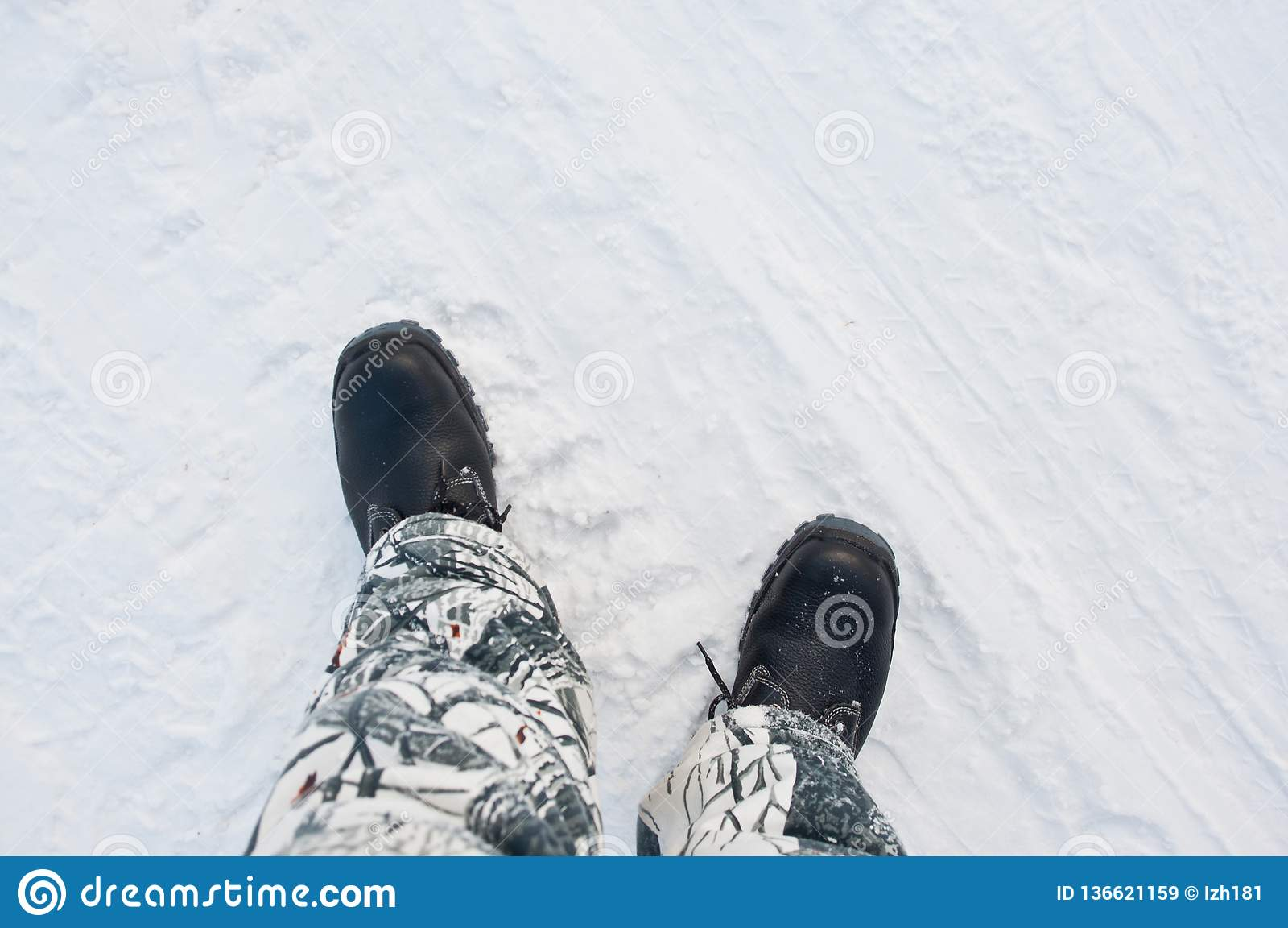 Varma arbetskängor på bakgrunden av en snöig väg