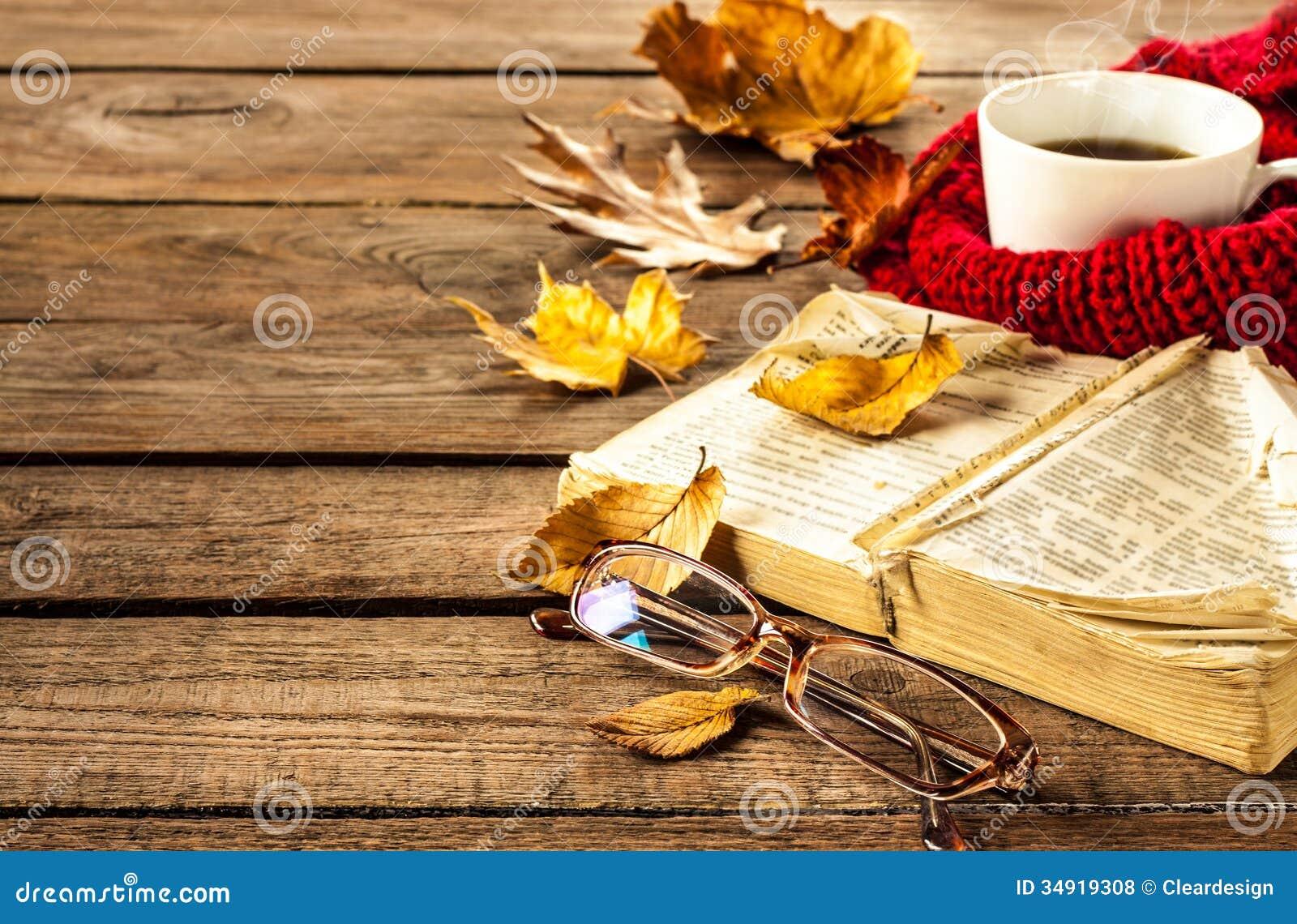 Varma kaffe, bok, exponeringsglas och höstsidor på wood bakgrund