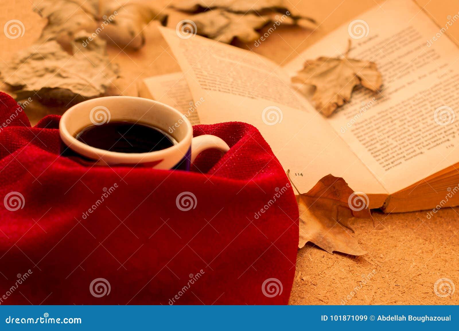 Varma kaffe, bok och höstsidor på wood bakgrund