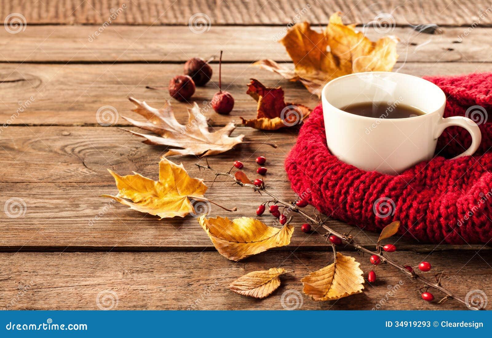 Varma kaffe och höstsidor på tappningträbakgrund