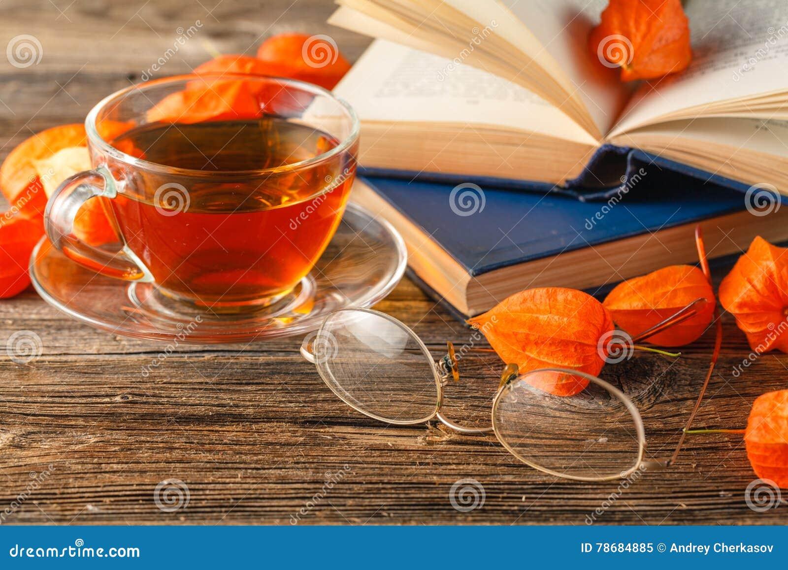 Varma kaffe, tappningbok, exponeringsglas och höstsidor på träbaksida