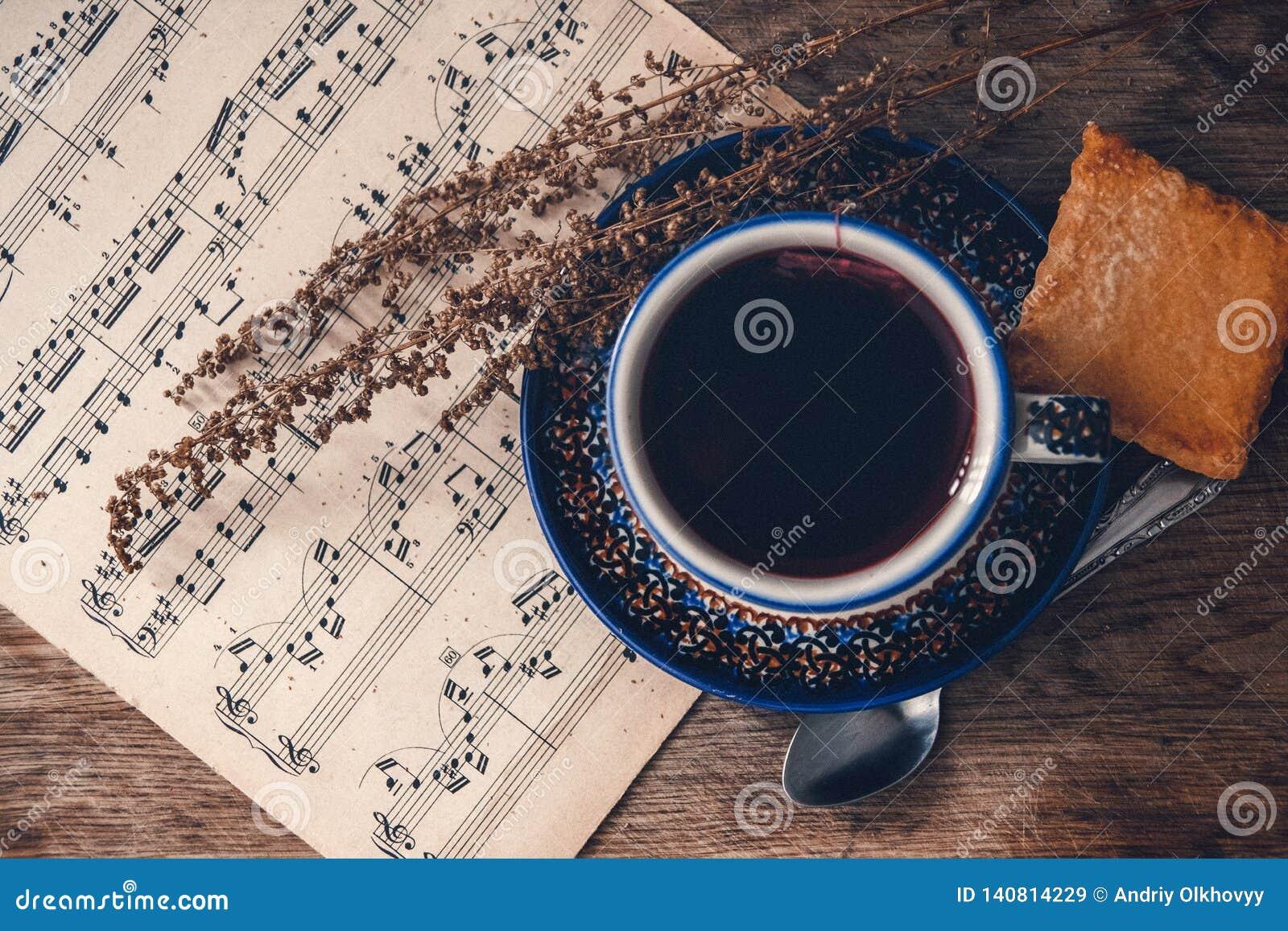 Varmt drink och kex med musikaliska anmärkningar och höstsidor på en trätabellyttersida Top beskådar