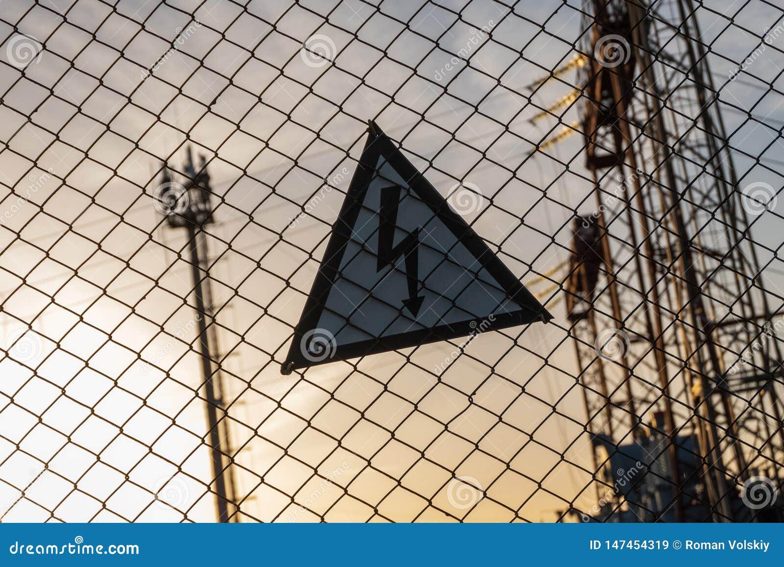 Varnande triangulärt tecken med en blixtbild på det netto staketet Farligt - hög spänning elektrisk avdelningskontor