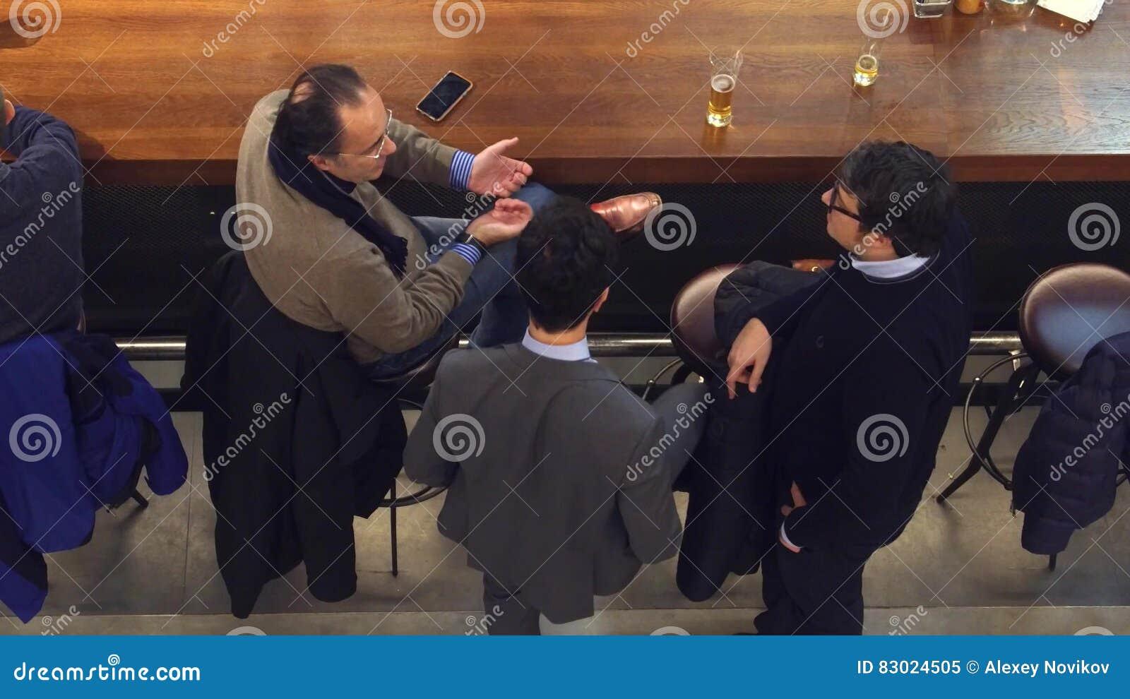 VARSÓVIA, POLÔNIA - DEZEMBRO, 22, 2016 homens de negócios Meados de-envelhecidos que têm a conversação na barra, tiro da vista su