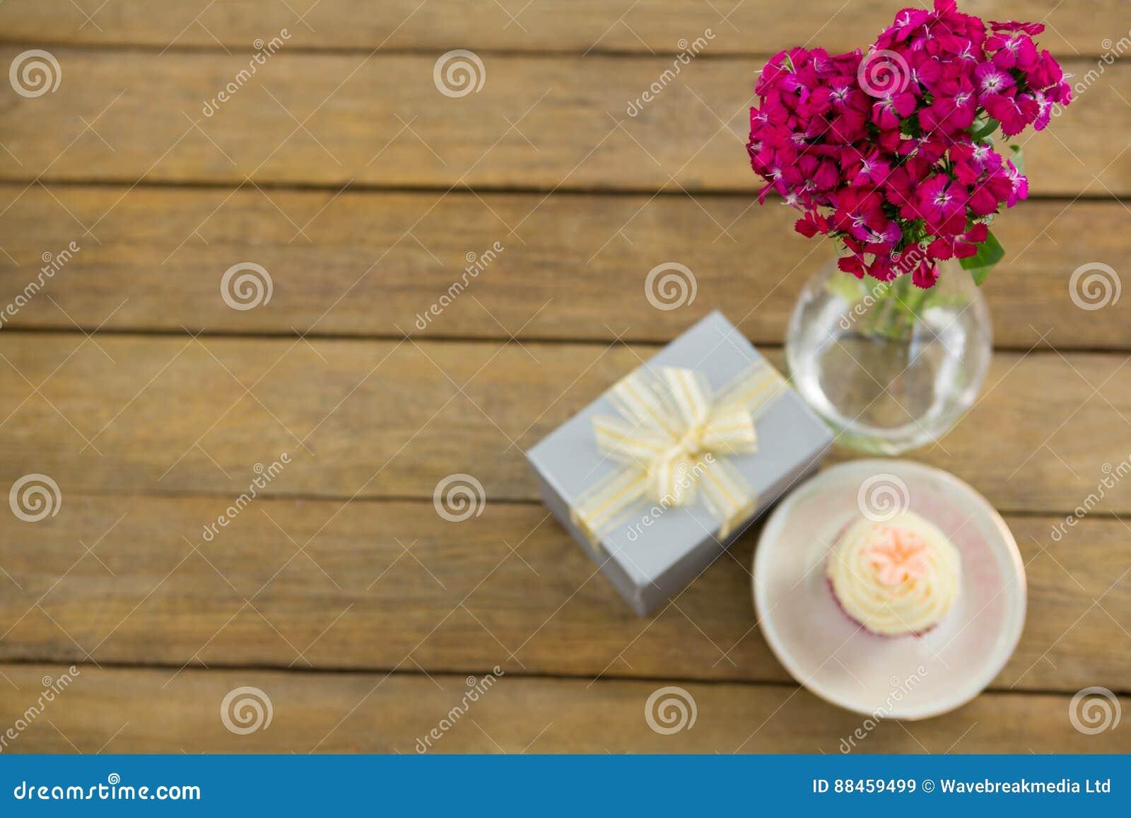 vase à boîte-cadeau et à fleur avec le petit gâteau dans le plat sur