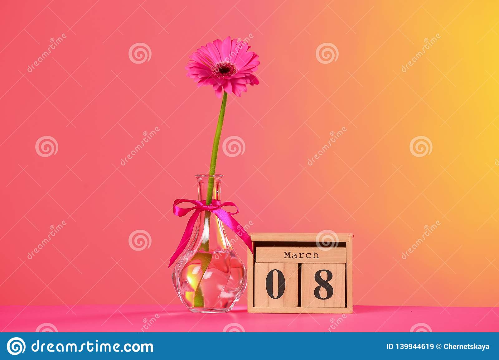 Vase with beautiful flower and wooden block calendar on table against color background