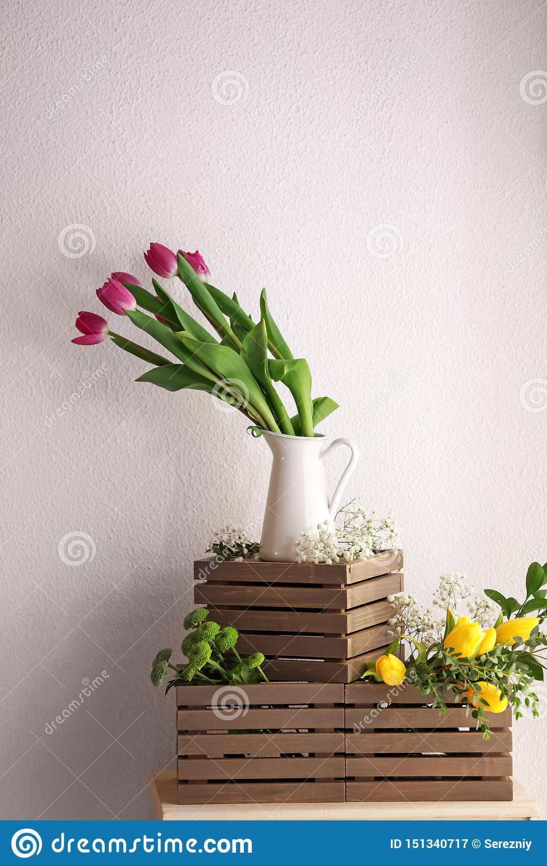 Vase with beautiful tulips and other flowers on wooden boxes