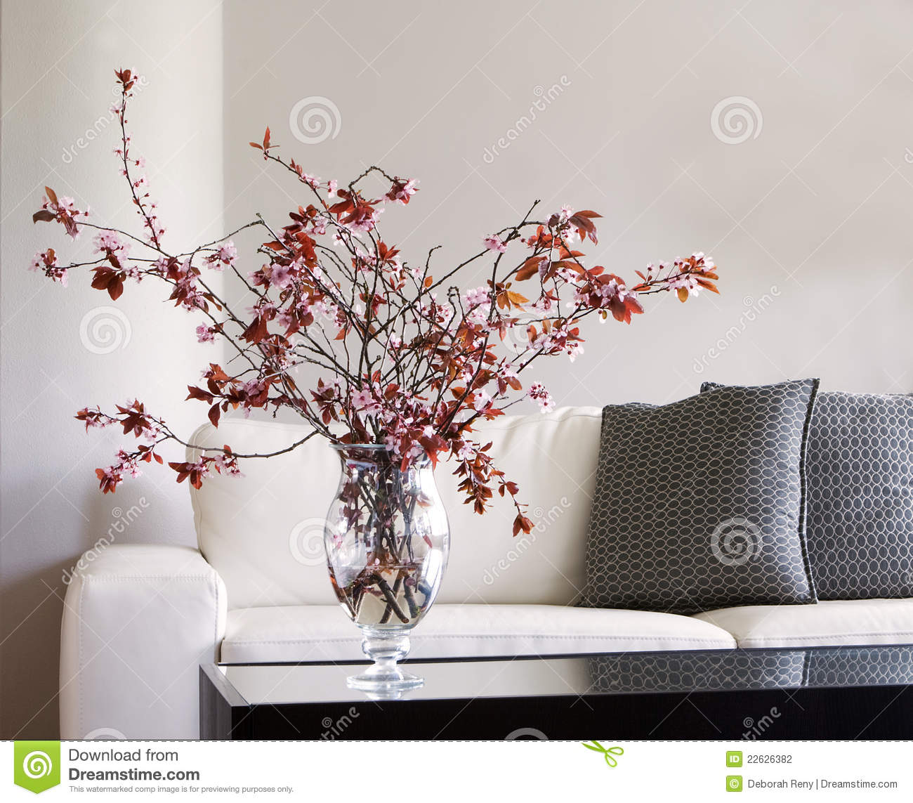 Vase Of Blossoms On Table In Modern Living Room Stock