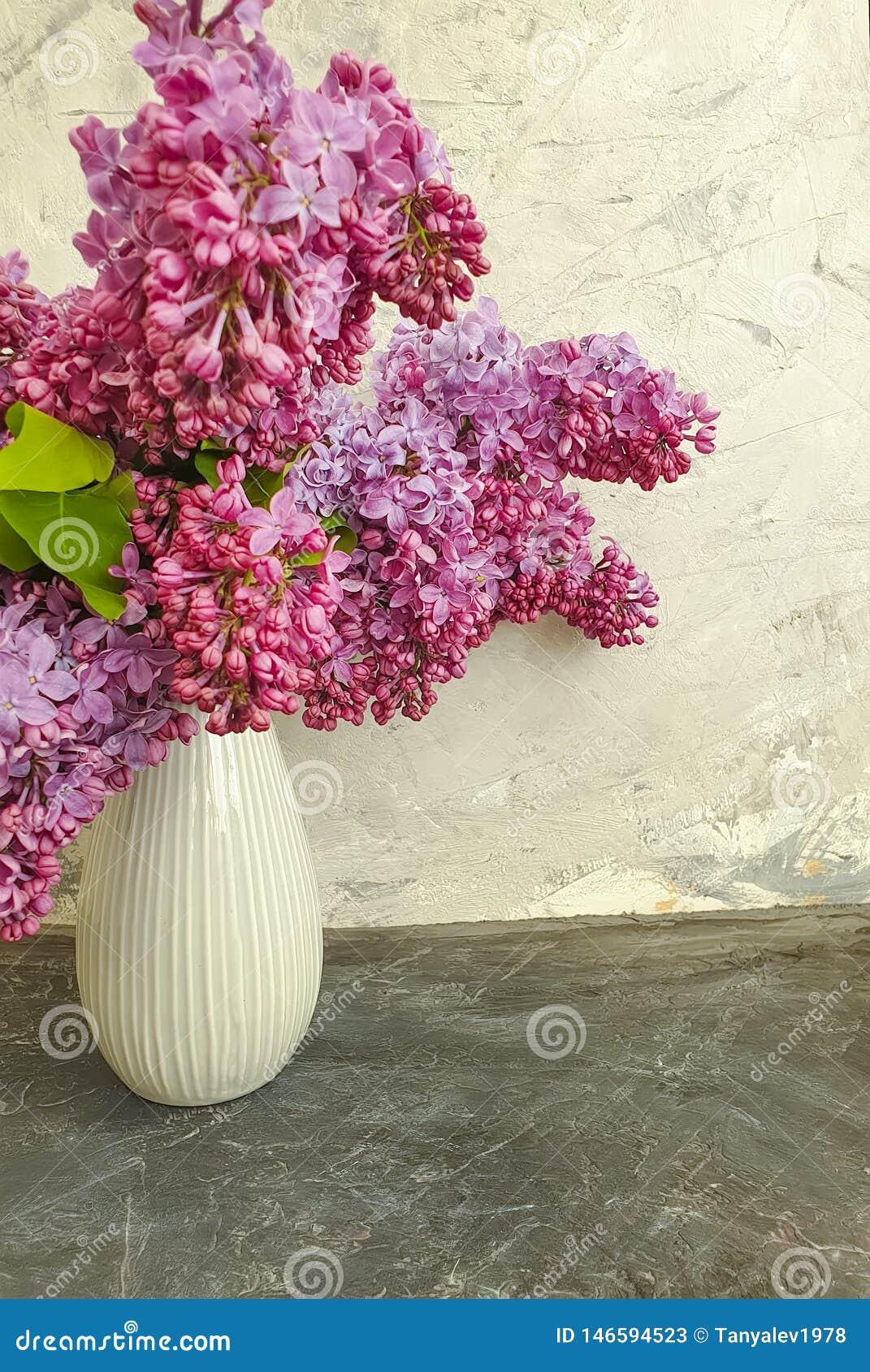 Vase bouquet of lilac on gray concrete