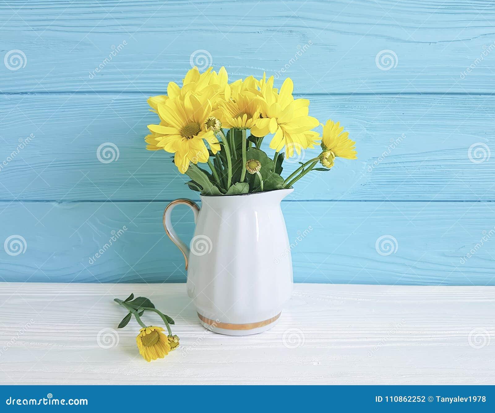 Vase jaune à chrysanthème sur vibrant blanc et bleu