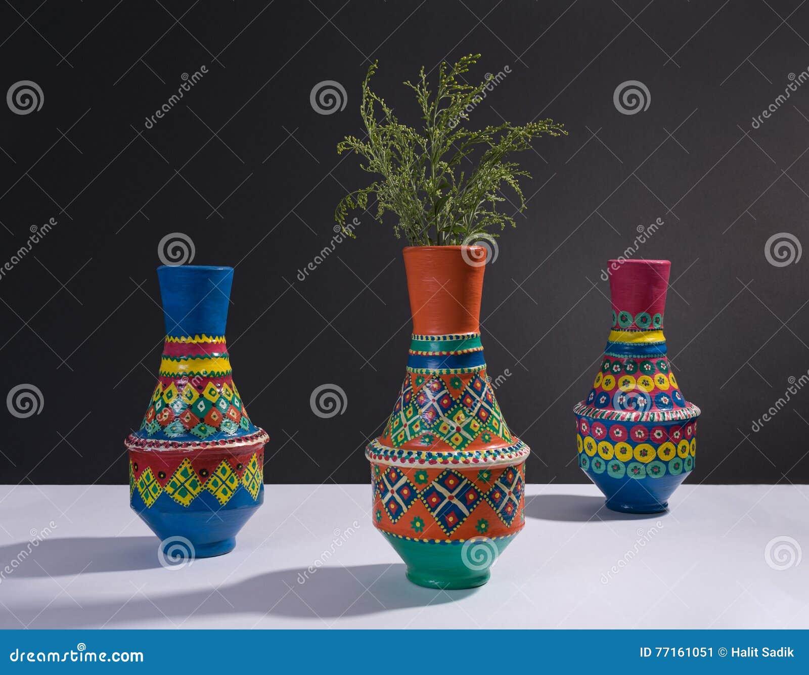 Vases handcrafted colorés à poterie et branches vertes avec l ombre dure