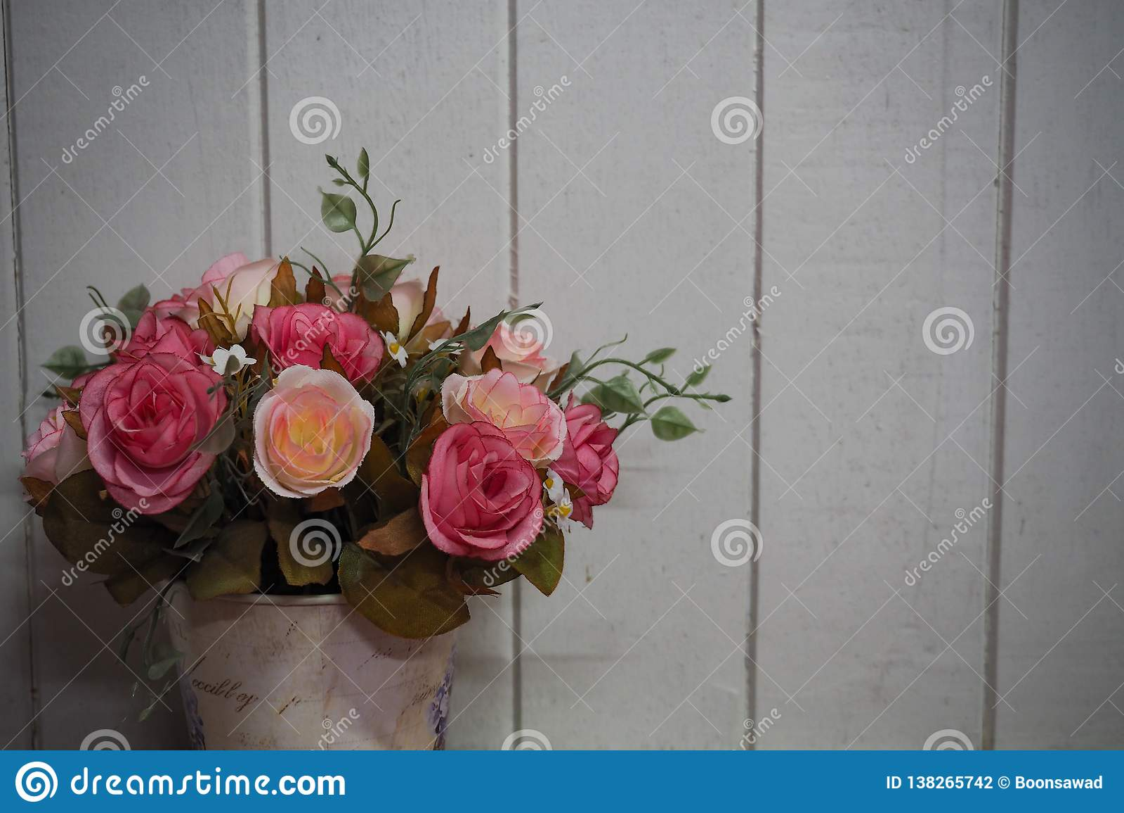 Vaso con il fondo di legno bianco della plancia delle rose