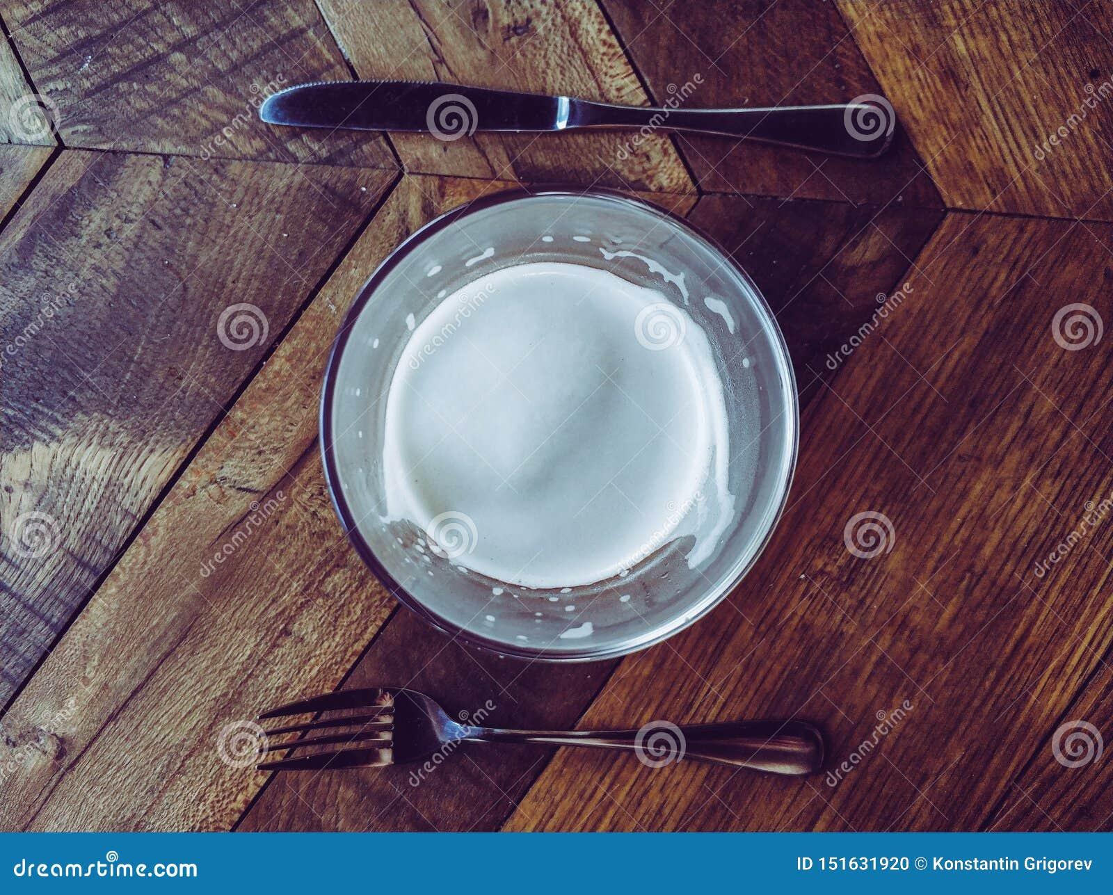 Vaso de cerveza, bifurcación y cuchillo en la tabla de madera