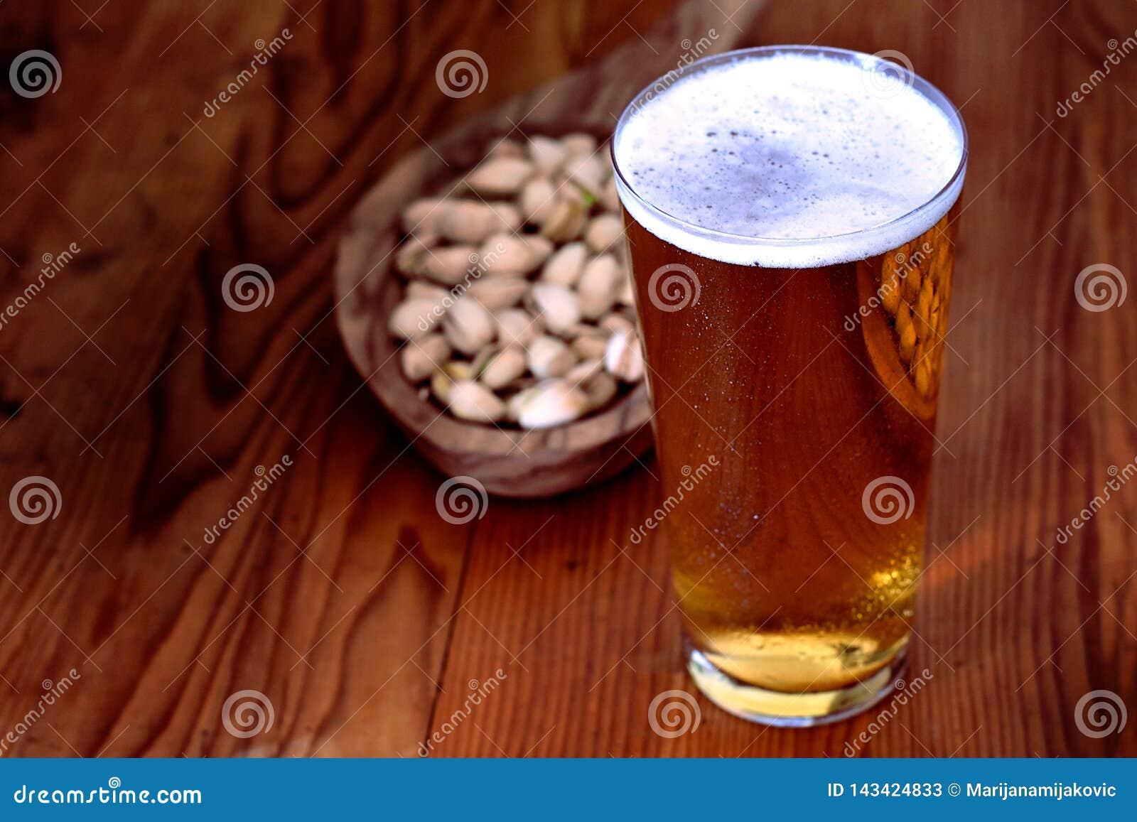 Vaso de cerveza con el pistacho