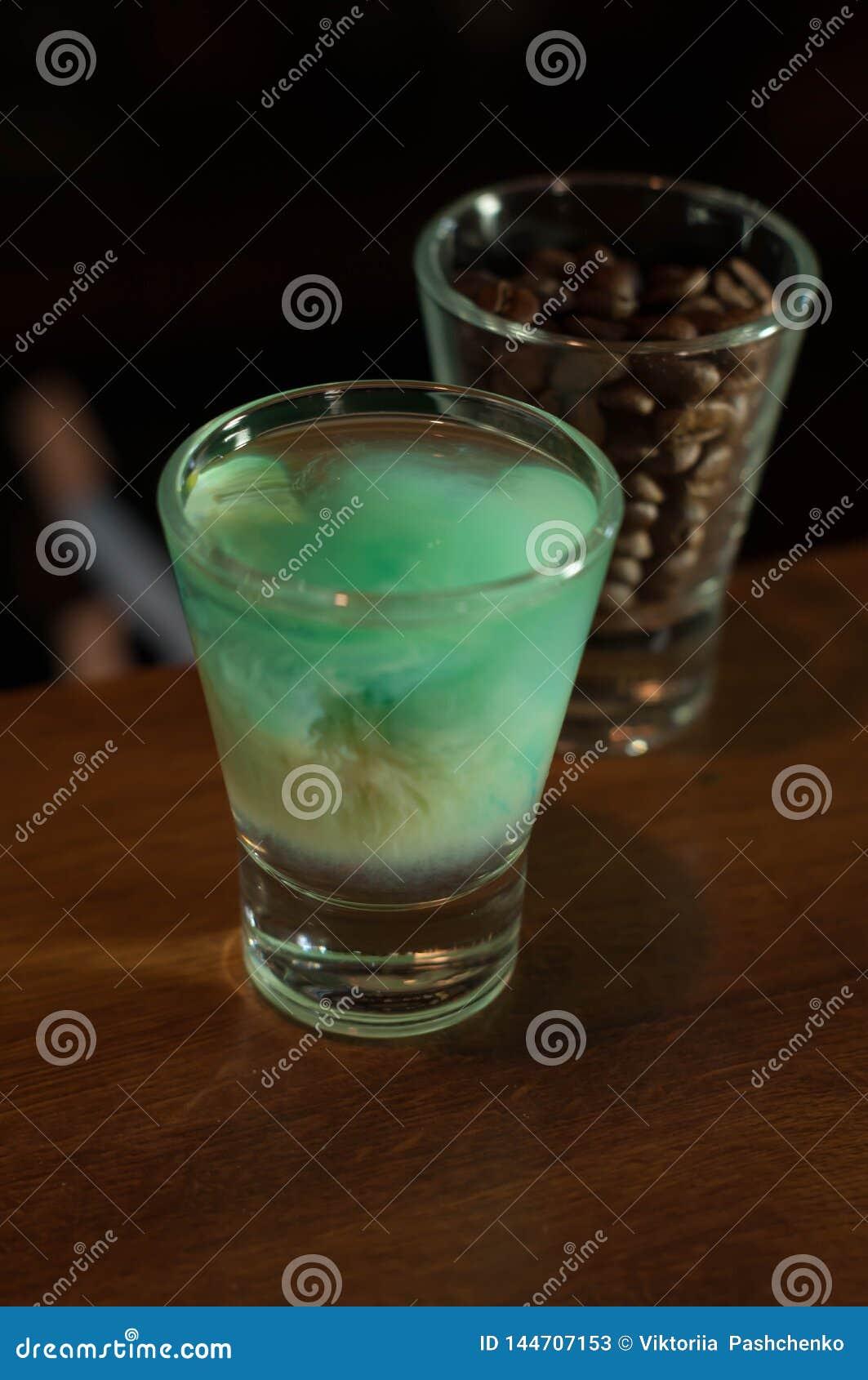 Vaso de medida con la bebida azul del alcohol cerca del vidrio con los granos de café