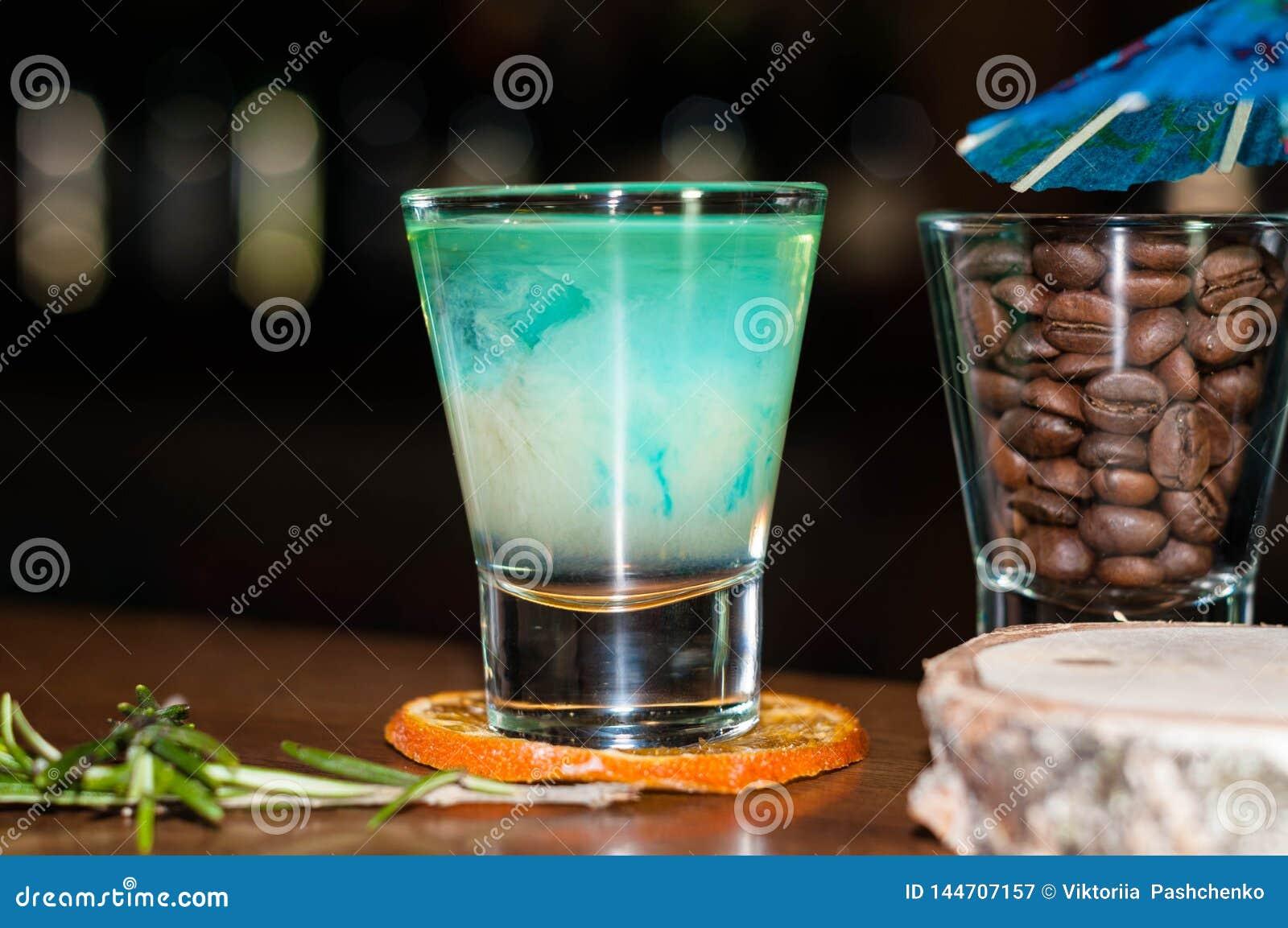 Vaso de medida con la bebida azul del alcohol en rebanada anaranjada secada con romero cerca del vidrio con los granos de café