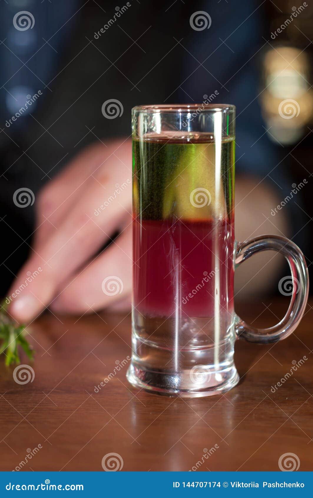 Vaso de medida con la bebida del alcohol y romero en contador de madera