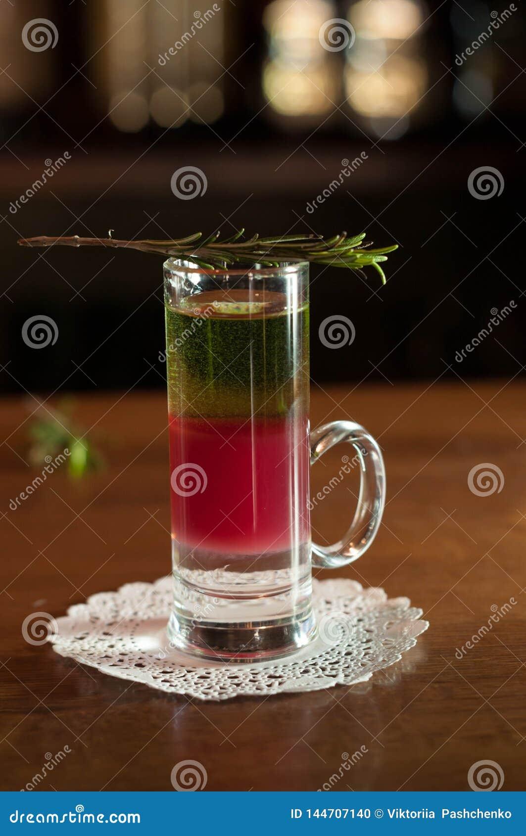 Vaso de medida con la bebida multicolora del alcohol y romero en la servilleta blanca