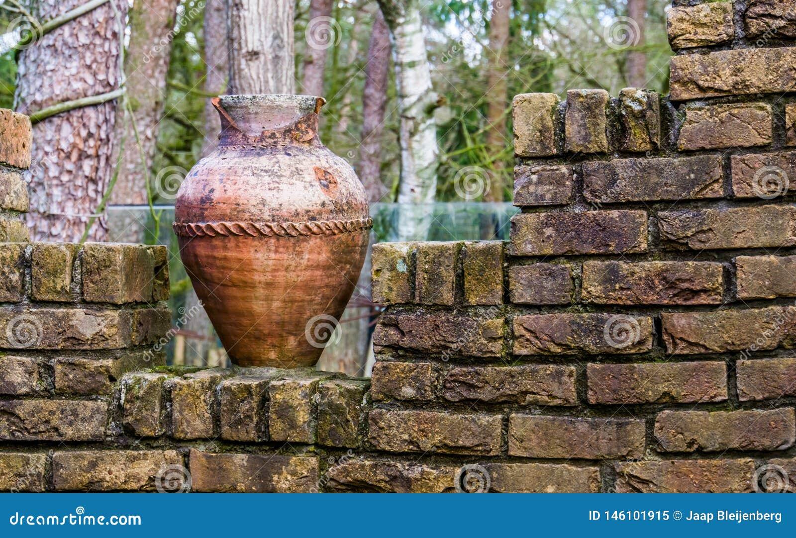 Vaso romano lascado velho em uma parede de tijolo, em umas decorações exteriores do jardim e em uma arquitetura