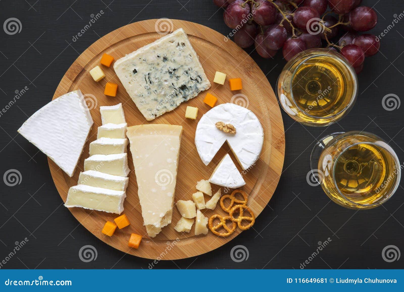 Vassoio del formaggio con vino, l uva, le ciambelline salate e le noci su fondo scuro, da sopra Vista superiore