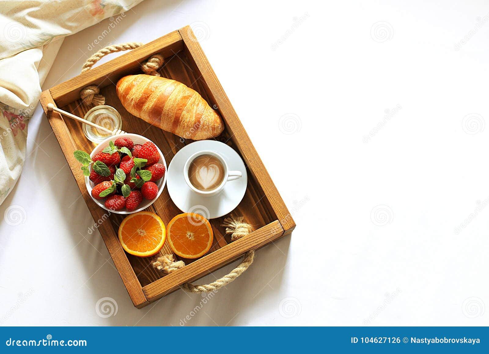 Vassoio della prima colazione a letto con la tazza di caffè, il croissant francese fresco ed i frutti sulla vista superiore dello