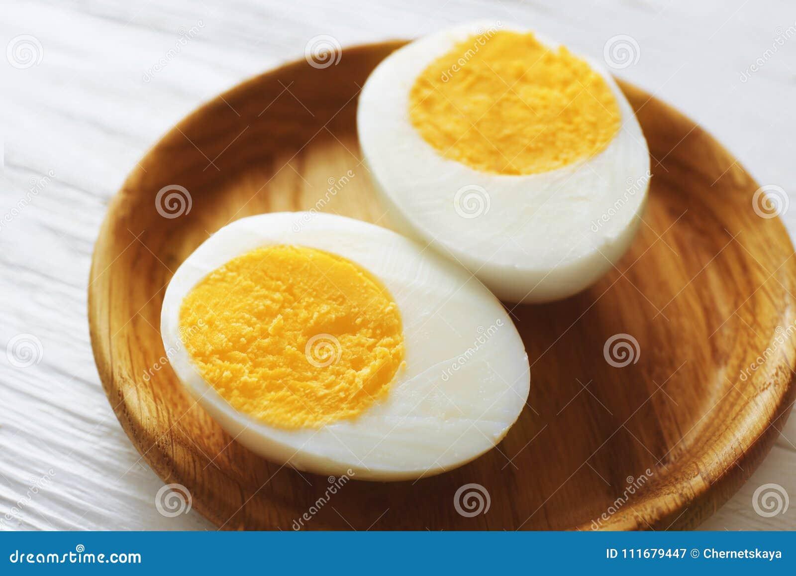 Vassoio di legno con l uovo sodo affettato sulla tavola bianca