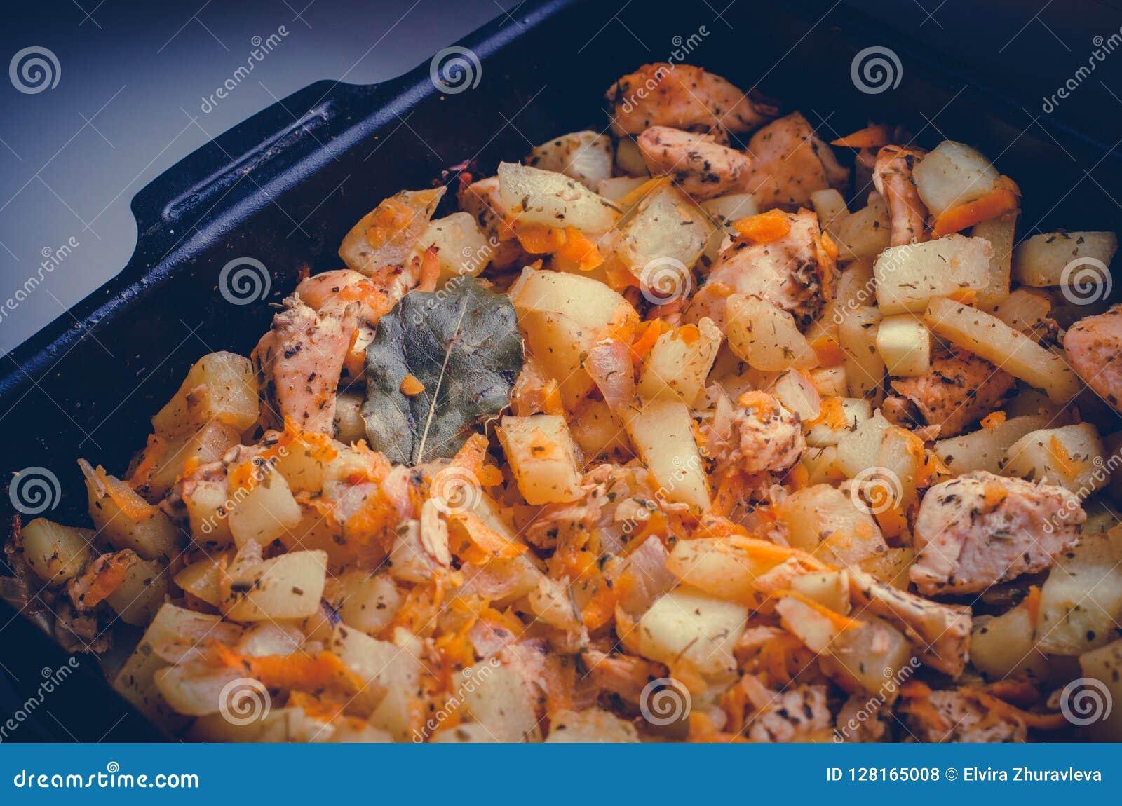 Vassoio di pasto casalingo con la fine delle patate, della carne, della carota, dello zucchini e della foglia di alloro su