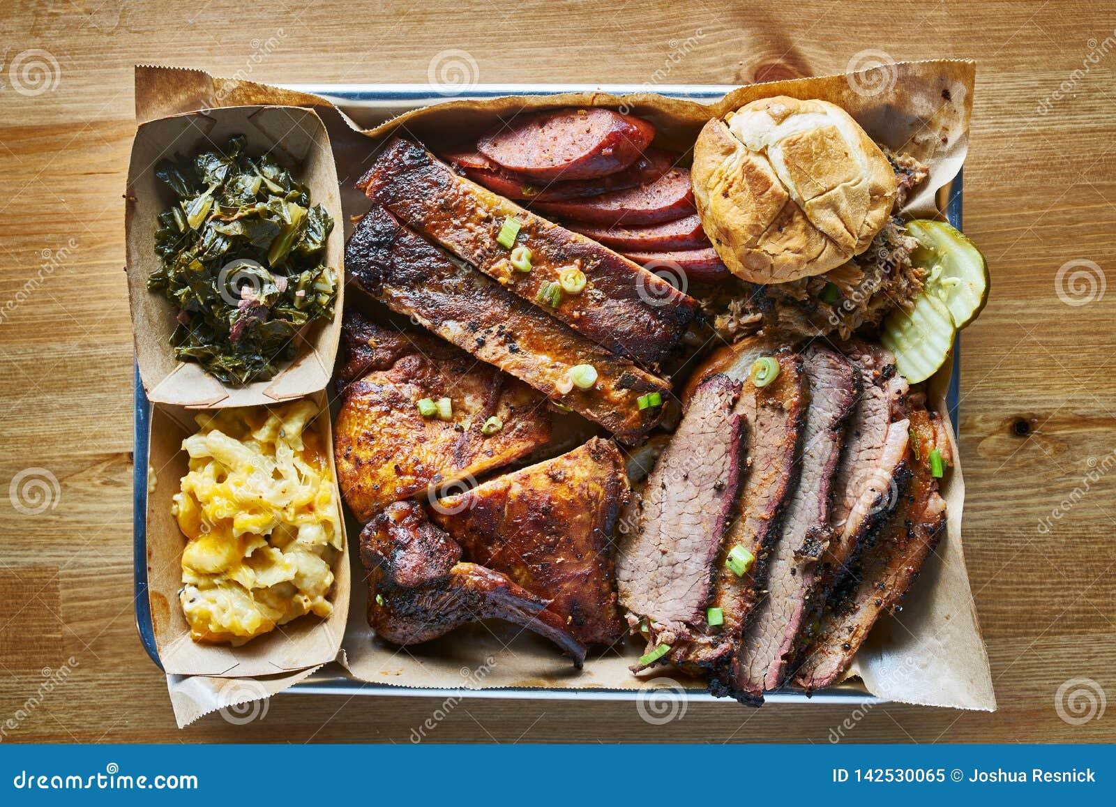 Vassoio di stile del bbq del Texas con il petto di manzo affumicato, le costole di St. Louis, il pollo ed i collegamenti caldi