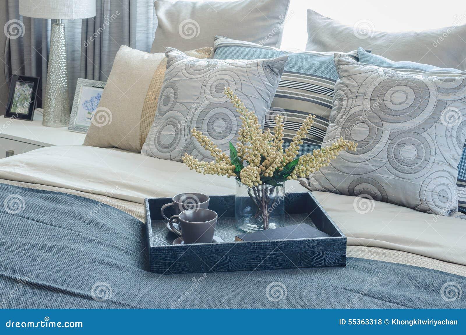 Vassoio di vaso di vetro e della tazza della pianta sul letto