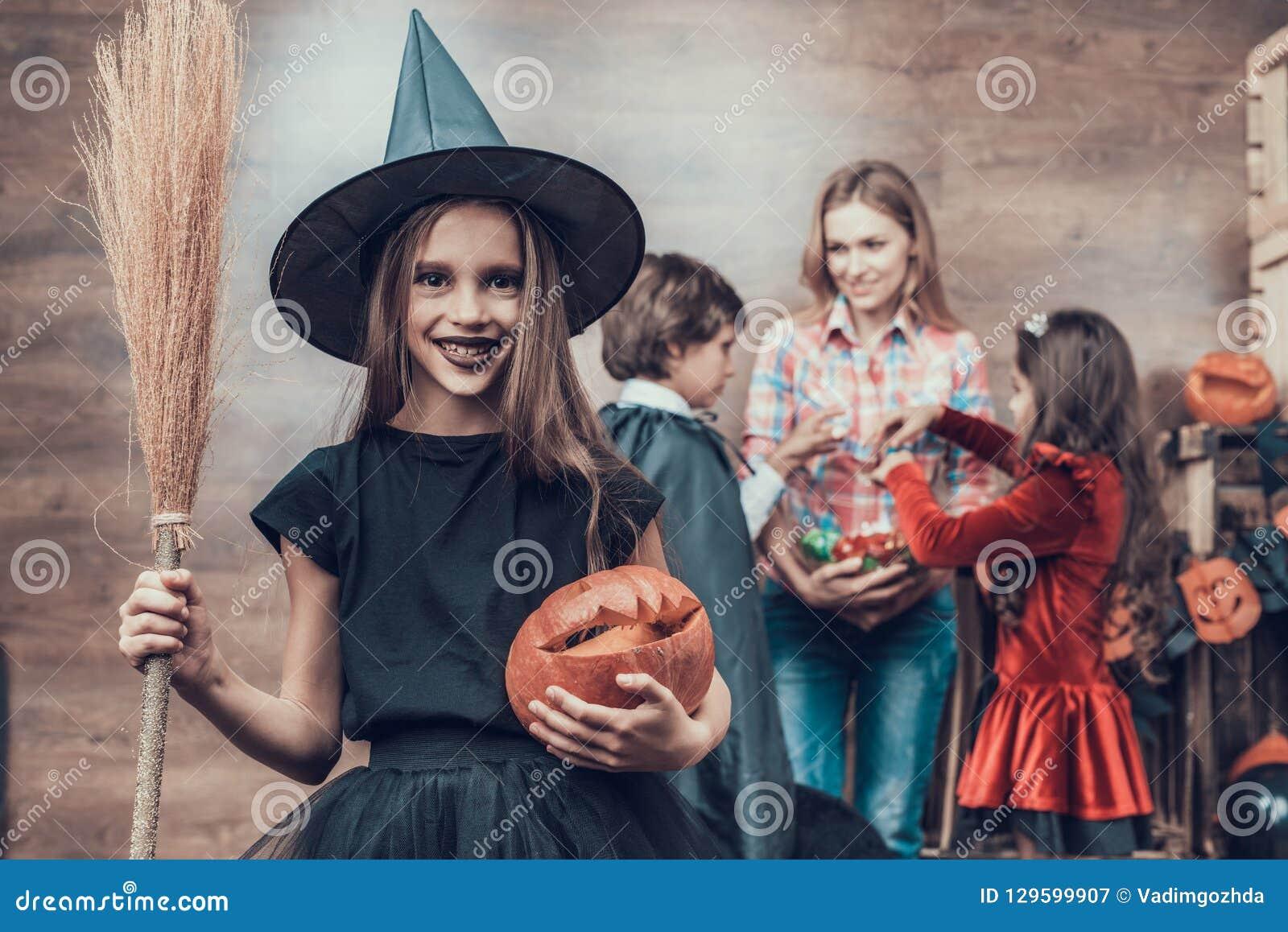 Vassoura vestindo da terra arrendada do traje da bruxa da moça