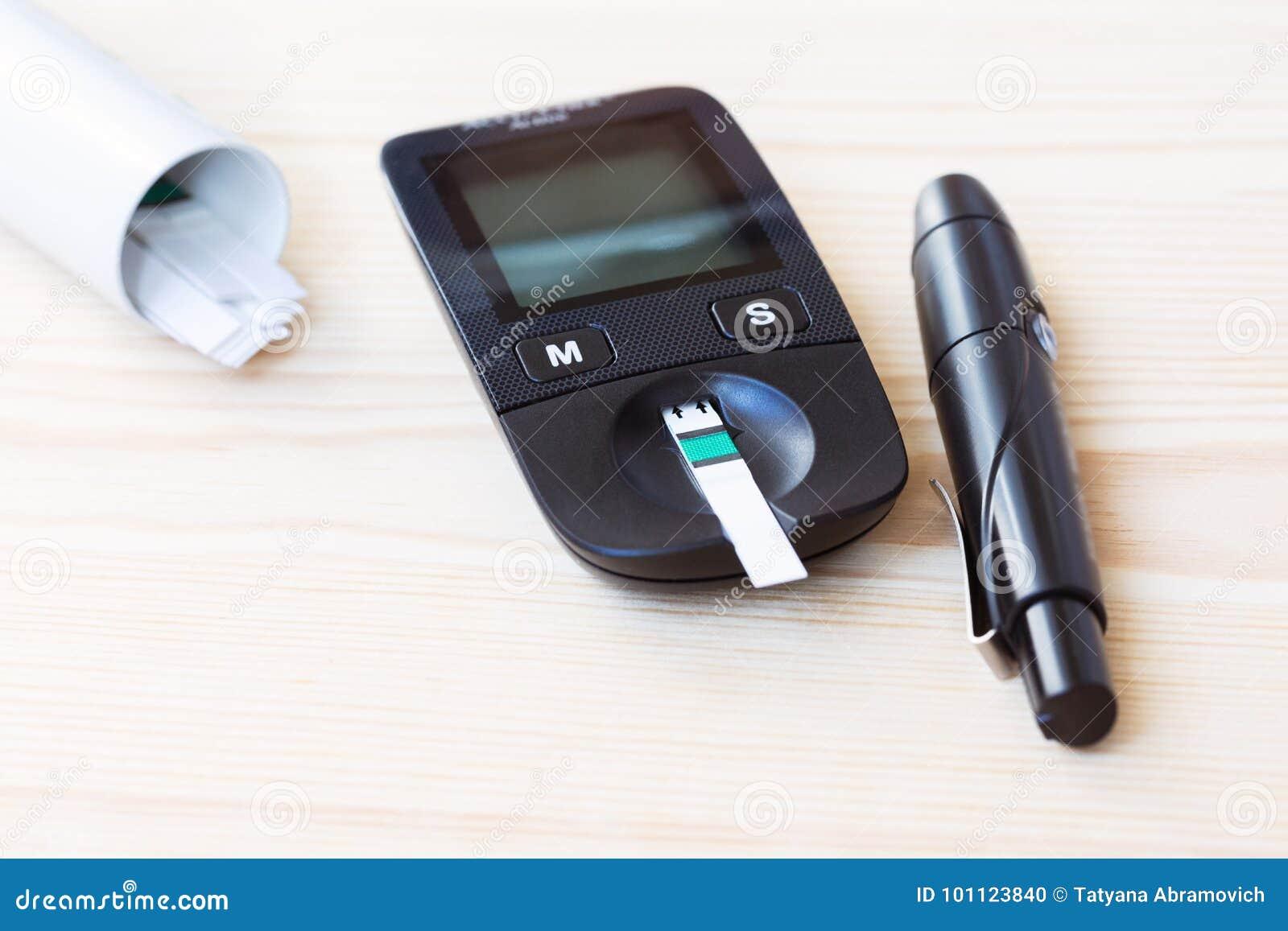 Vastgestelde glucometer en spuit met de Stroken van de Diabetesindicator voor Bloedglucose het Testen op houten achtergrond