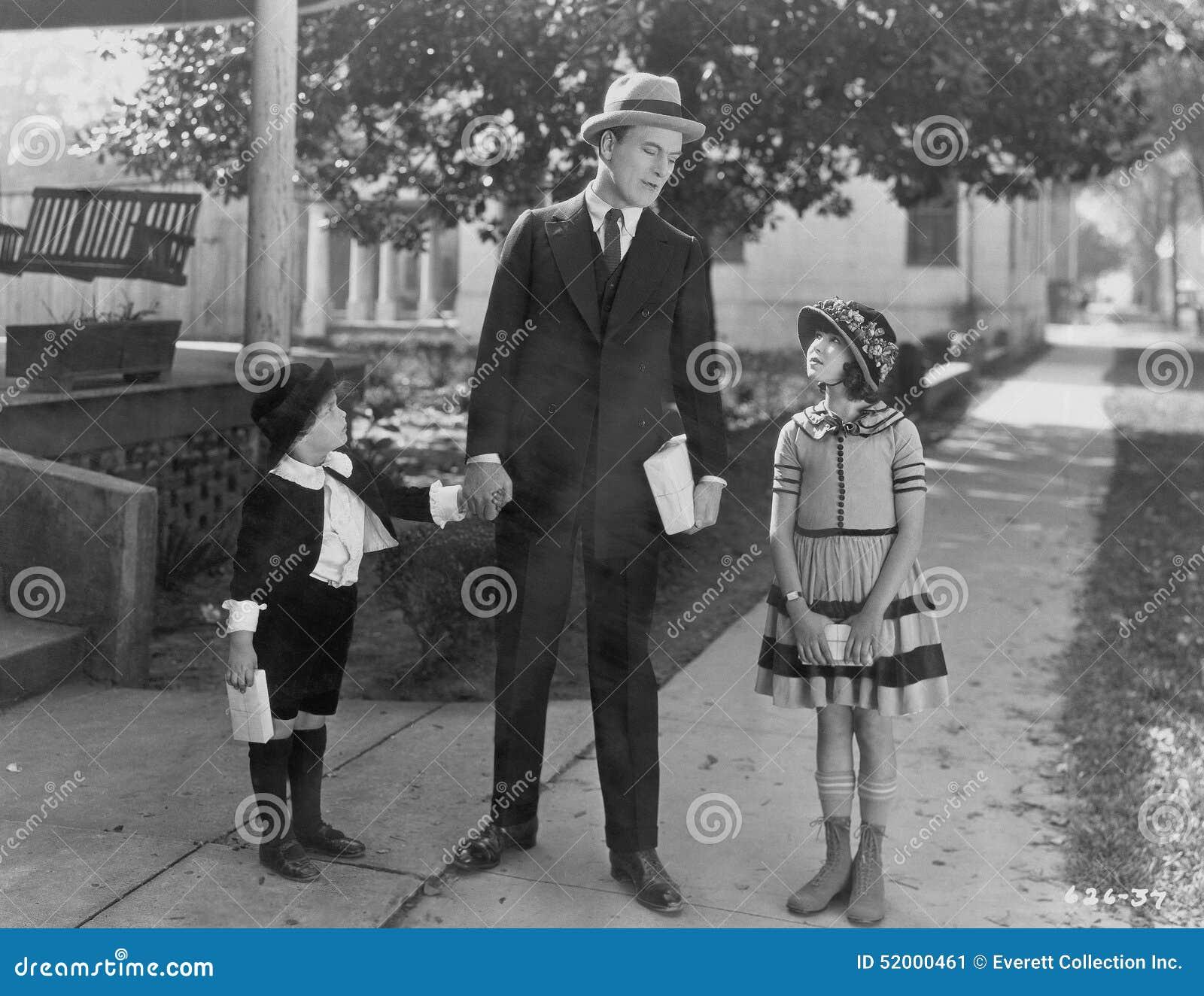 Vater, der mit der zwei Kinderaußenseite spricht (alle dargestellten Personen sind nicht längeres lebendes und kein Zustand exist